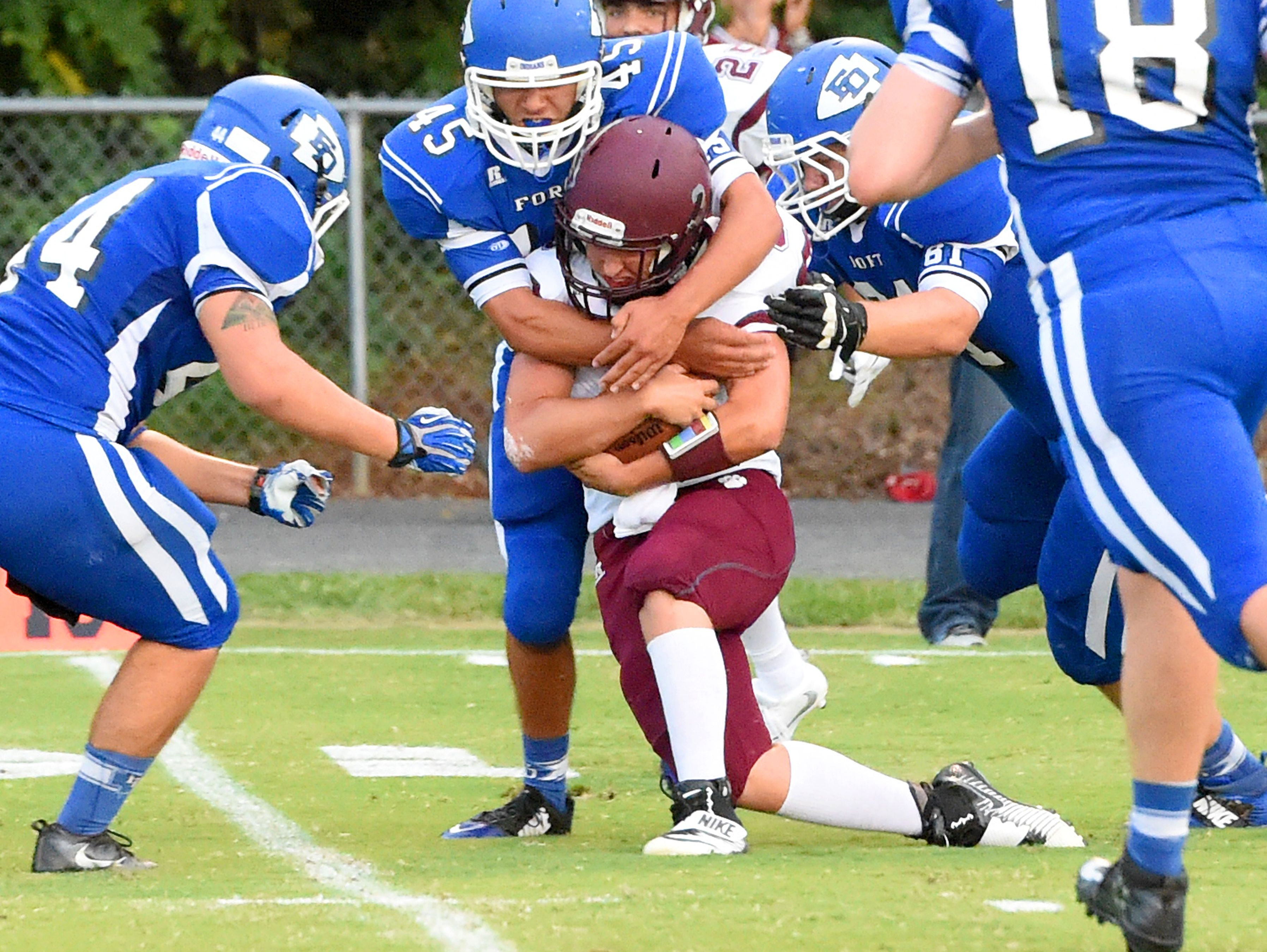 Stuarts Draft quarterback Garrett Campbell is wrapped up by Fort Defiance's Miguel Garcia during a football game played in Fort Defiance on Friday, Sept. 2, 2016.