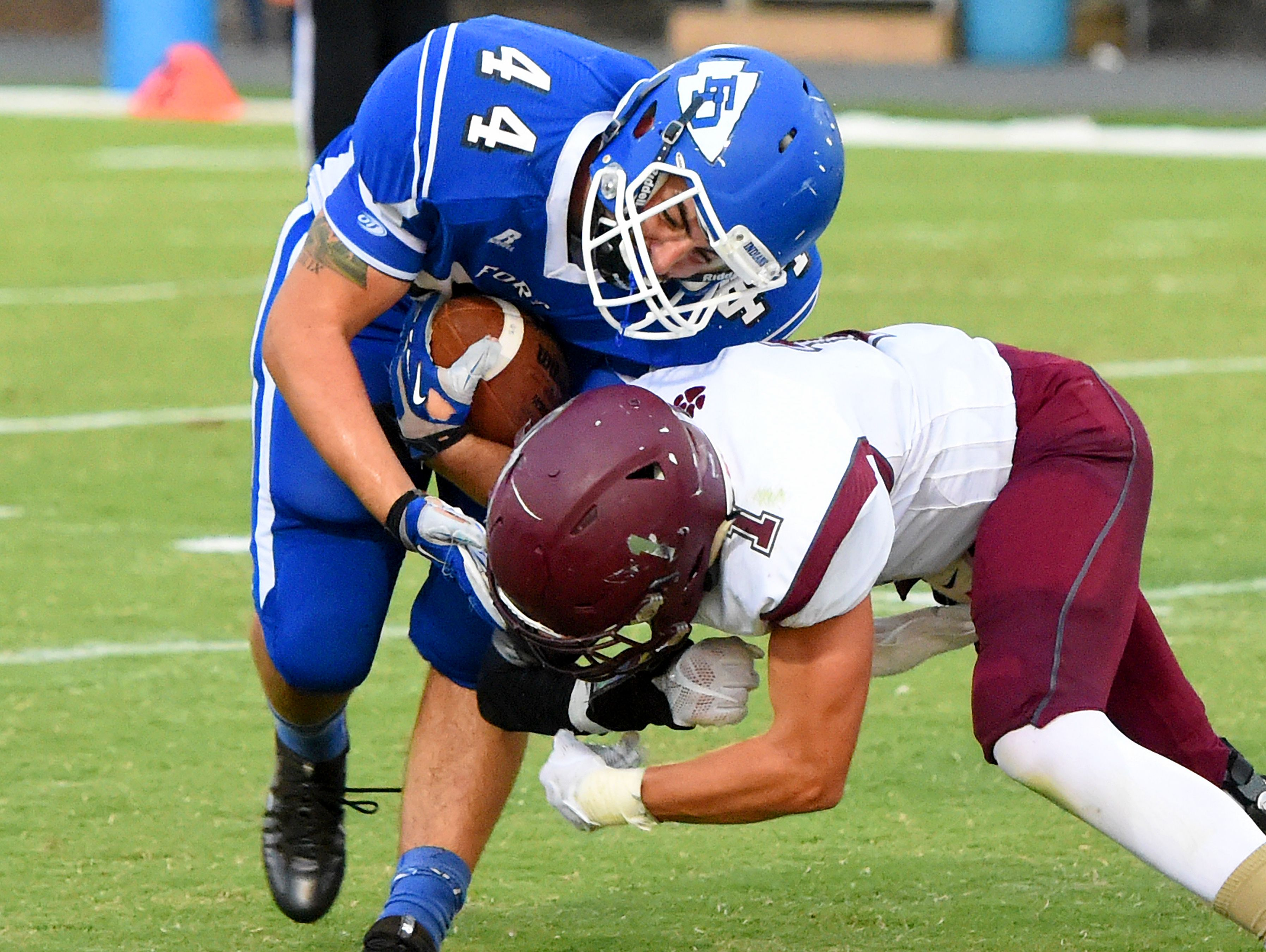 Fort Defiance's Austin Fitzwater holds onto the football as Stuarts Draft's Robert Peck slams into him for the tackle during a football game played in Fort Defiance on Friday, Sept. 2, 2016.