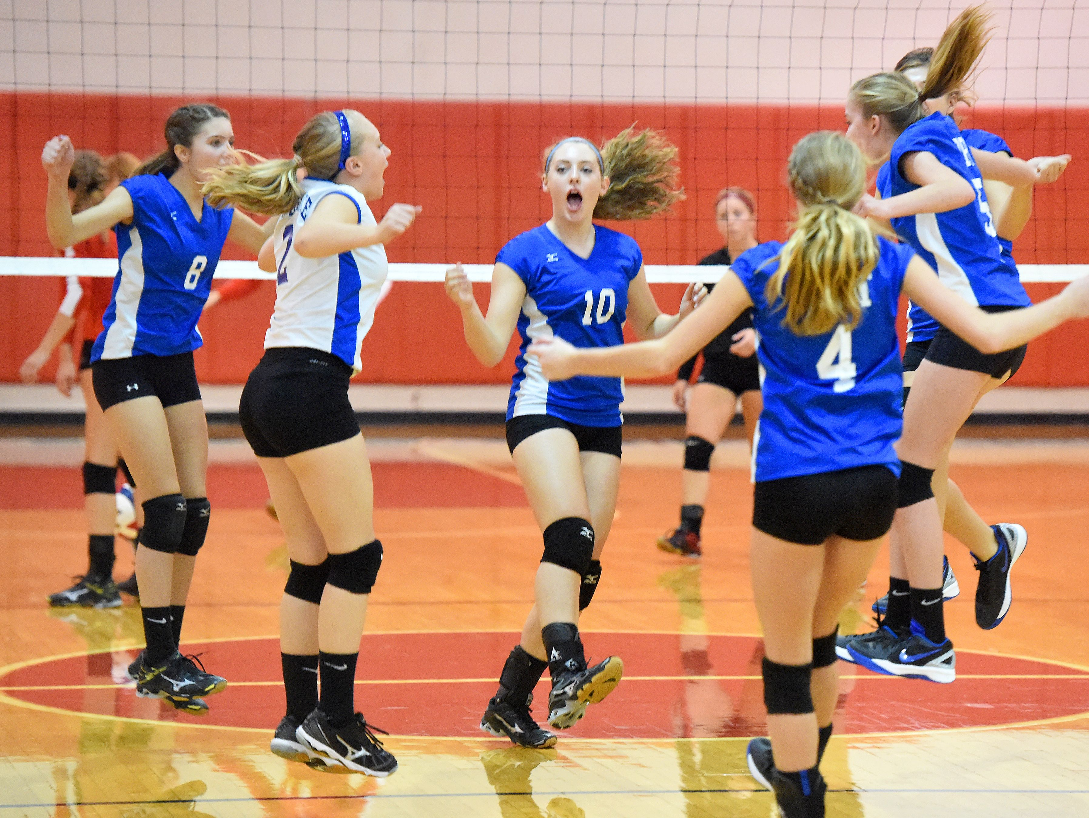 Fort Defiance's Catie Cramer (center) celebrates a point with her team on the court during a volleyball match played in Greenville on Thursday, Sept. 9, 2016.