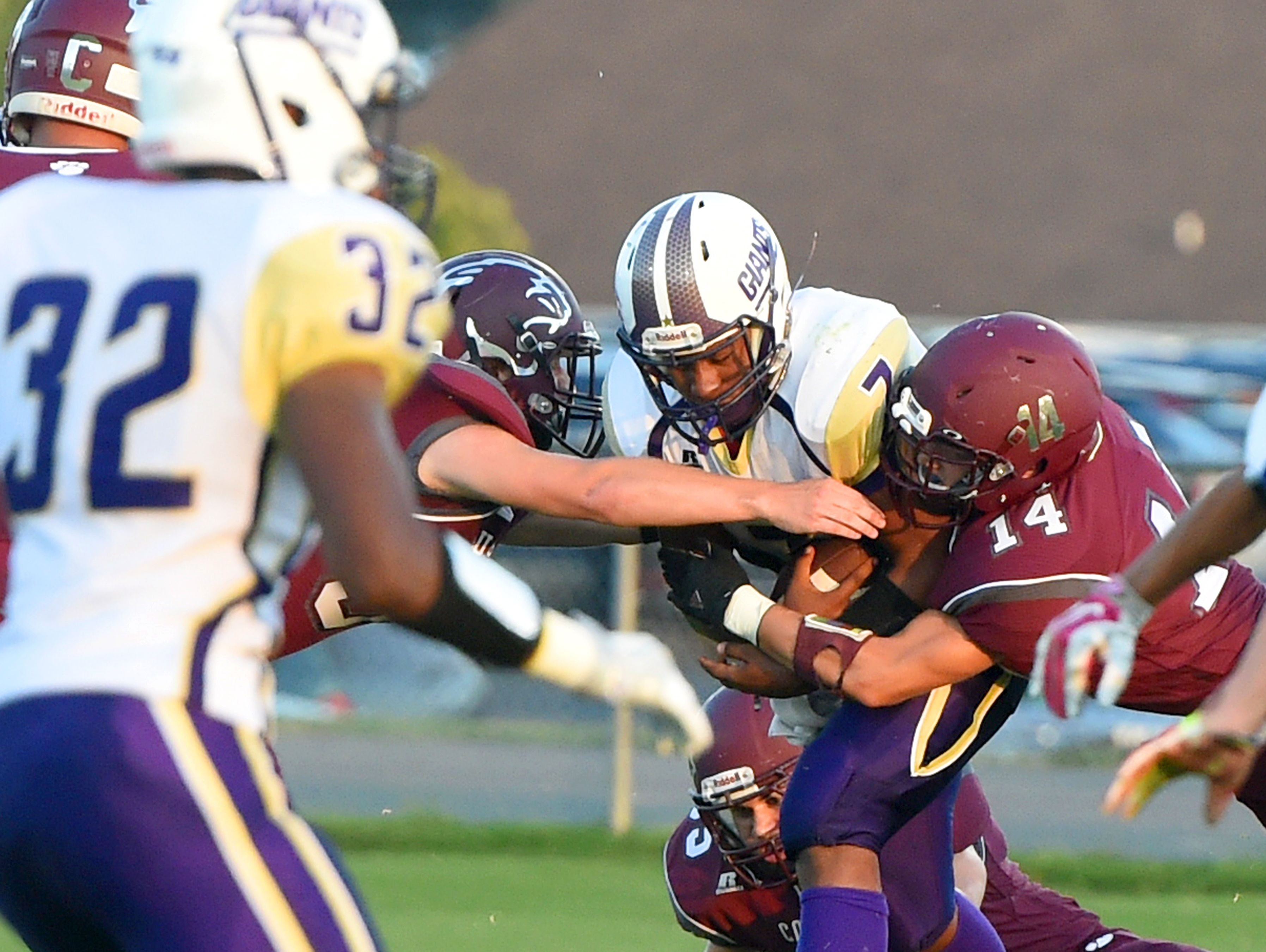 Waynesboro's DaJuan Moore protects the ball as he is wrapped up on either side by the Stuarts Draft defense during a football game played in Stuarts Draft on Friday, Sept. 9, 2016.