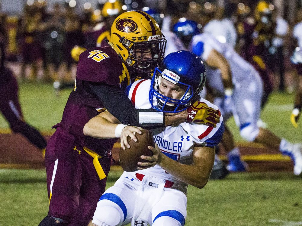 Mountain Pointe High School's Jacob Olsen tackles Chandler High's Jacob Conover for a big loss during first half action at Mountain Pointe on Thursday night.