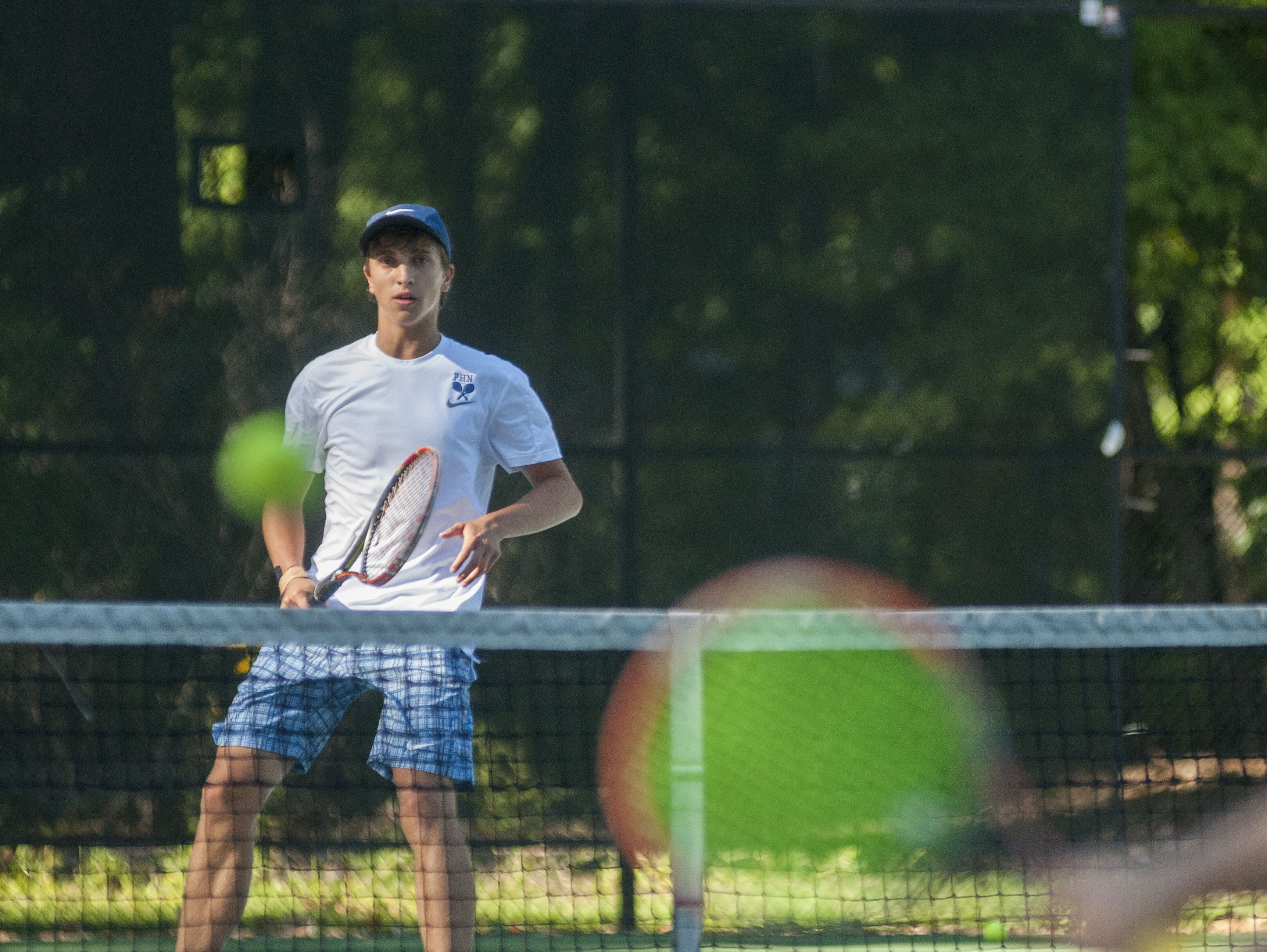 Huskies' John Betrus hits the ball over the net Monday, Sept. 12, during boys tennis action at Sanborn Park tennis courts.
