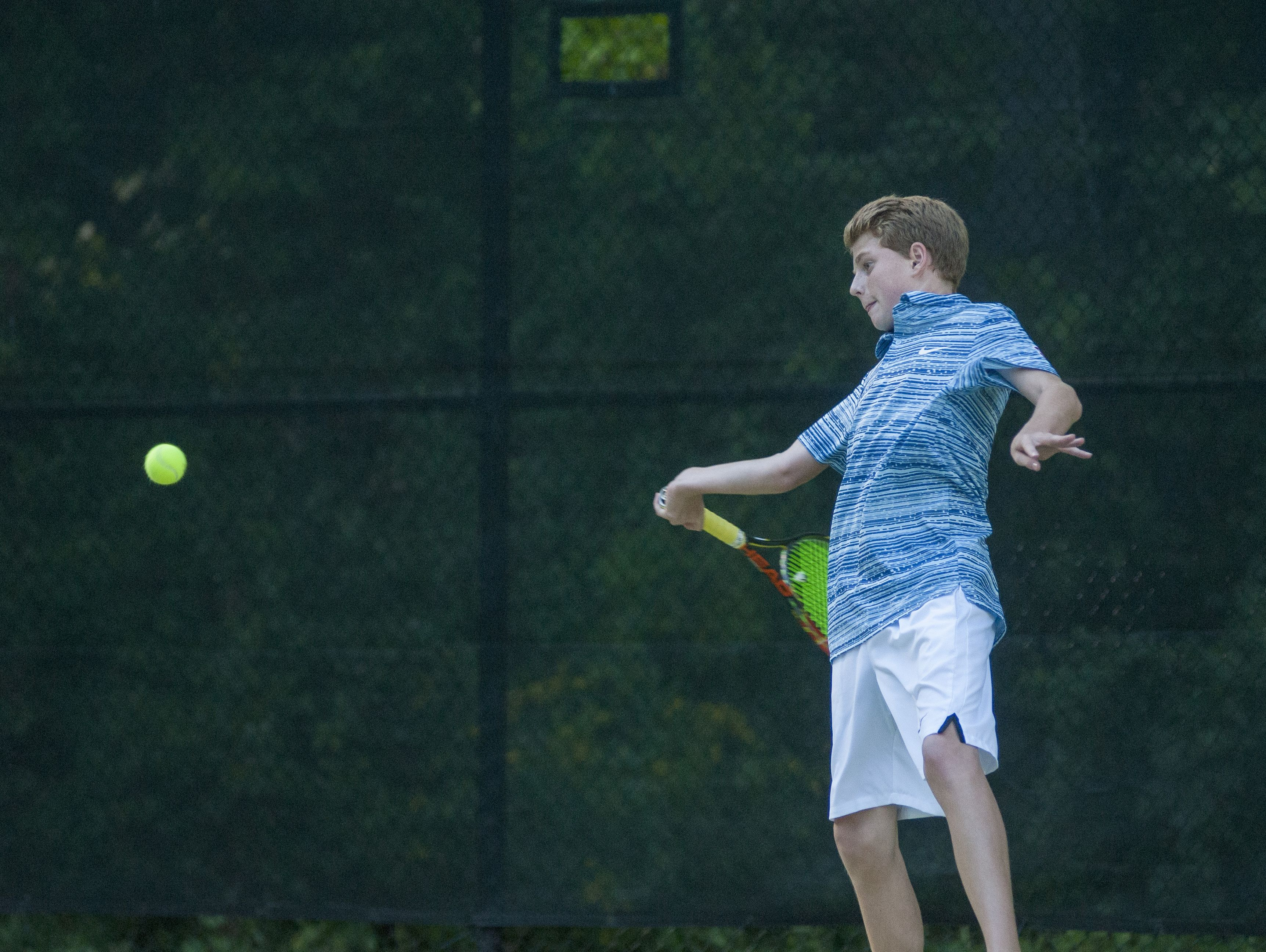 Saints' Eli Pinnoo readues a forehand return Monday, Sept. 12, during boys tennis action at Sanborn Park tennis courts.