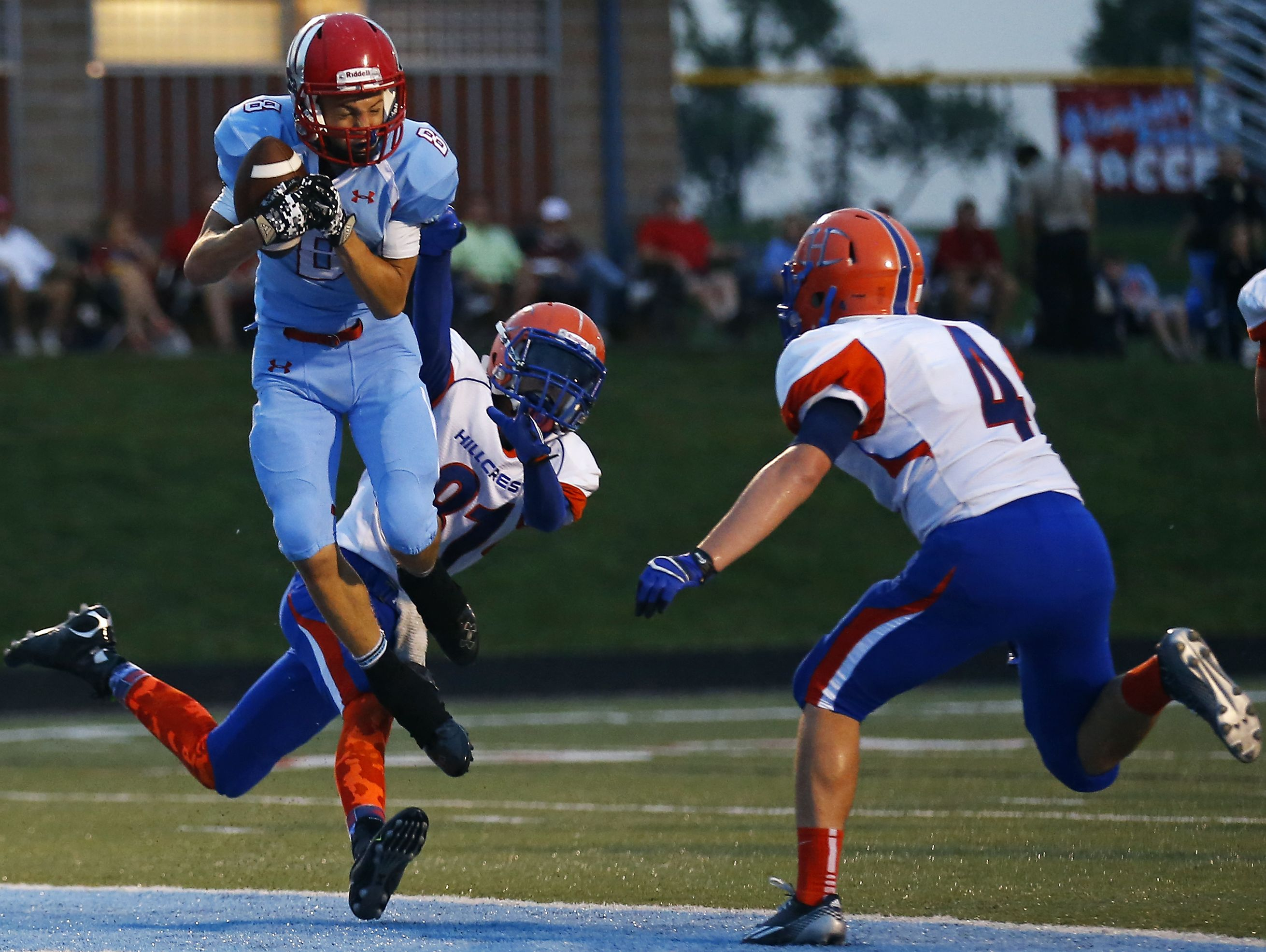 Glendale wide receiver Von Oeser (8) catches a touchdown pass between two Hillcrest defenders during the first quarter of a game at Lowe Stadium.
