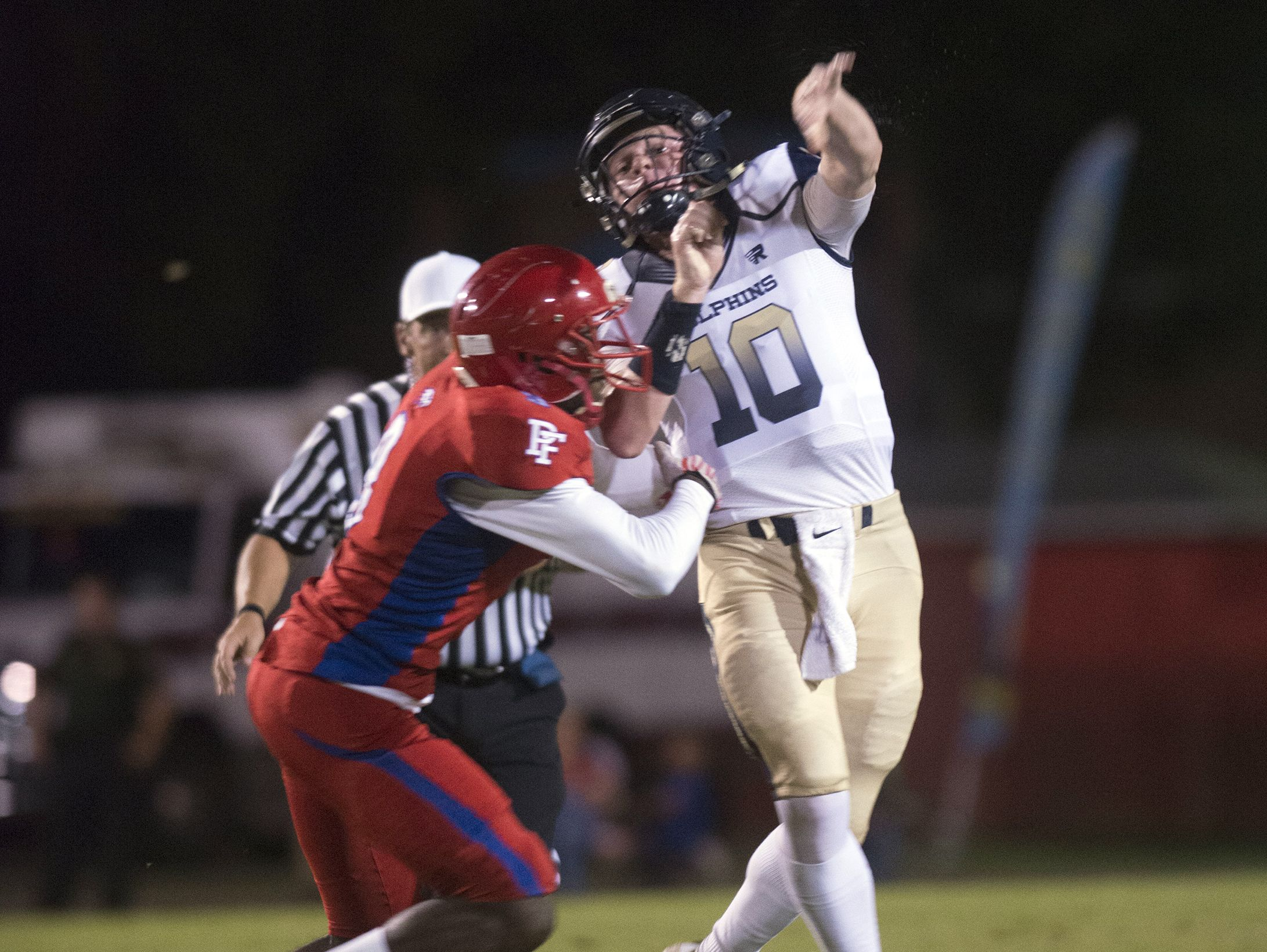 Gulf Breeze quarterback, Tyler Phelps, (No. 10) looks for an open receiver while under pressure from Pine Forest defensive end, Clarence Hicks,(No. 9) during Friday night's game against the Eagles.