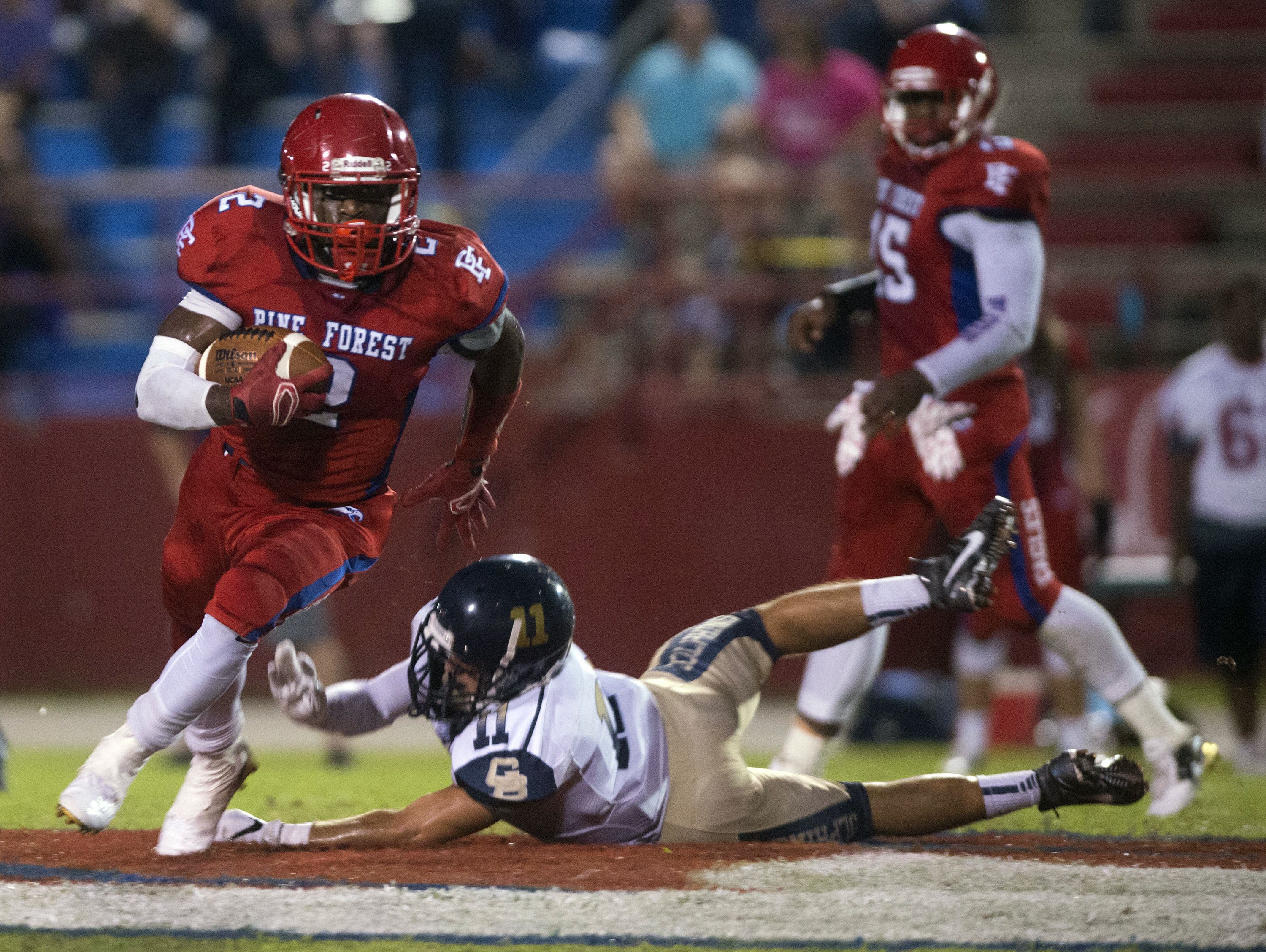 Pine Forest High running back Jaden Gardner, (No.2), slips away from the Gulf Breeze Line backer, Ben Dobry,(No. 11) during Friday night's home game against the Dolphins.