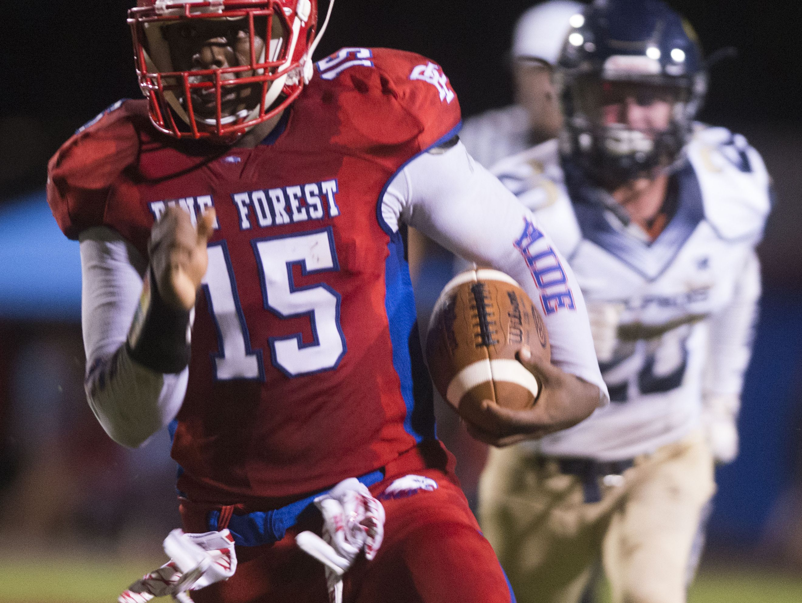 Pine Forest quarterback, Xavier Saulsberry, (No.15) finds a hole in the Gulf Breeze line for a gain in yards during Friday night's home game against Gulf Breeze.