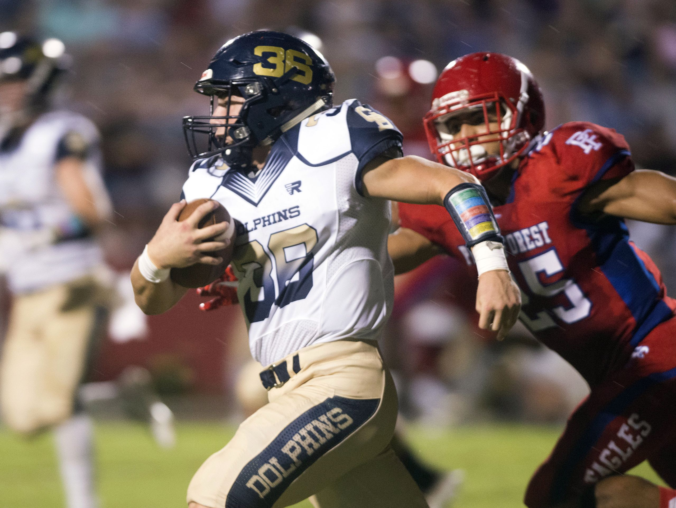 Gulf Breeze running back Tyler Dittmer, (No. 36) slips past the Pine Forest middle line backer, Nolan Rigby, (No. 25) to pick up extra yards against the Eagles Friday night.