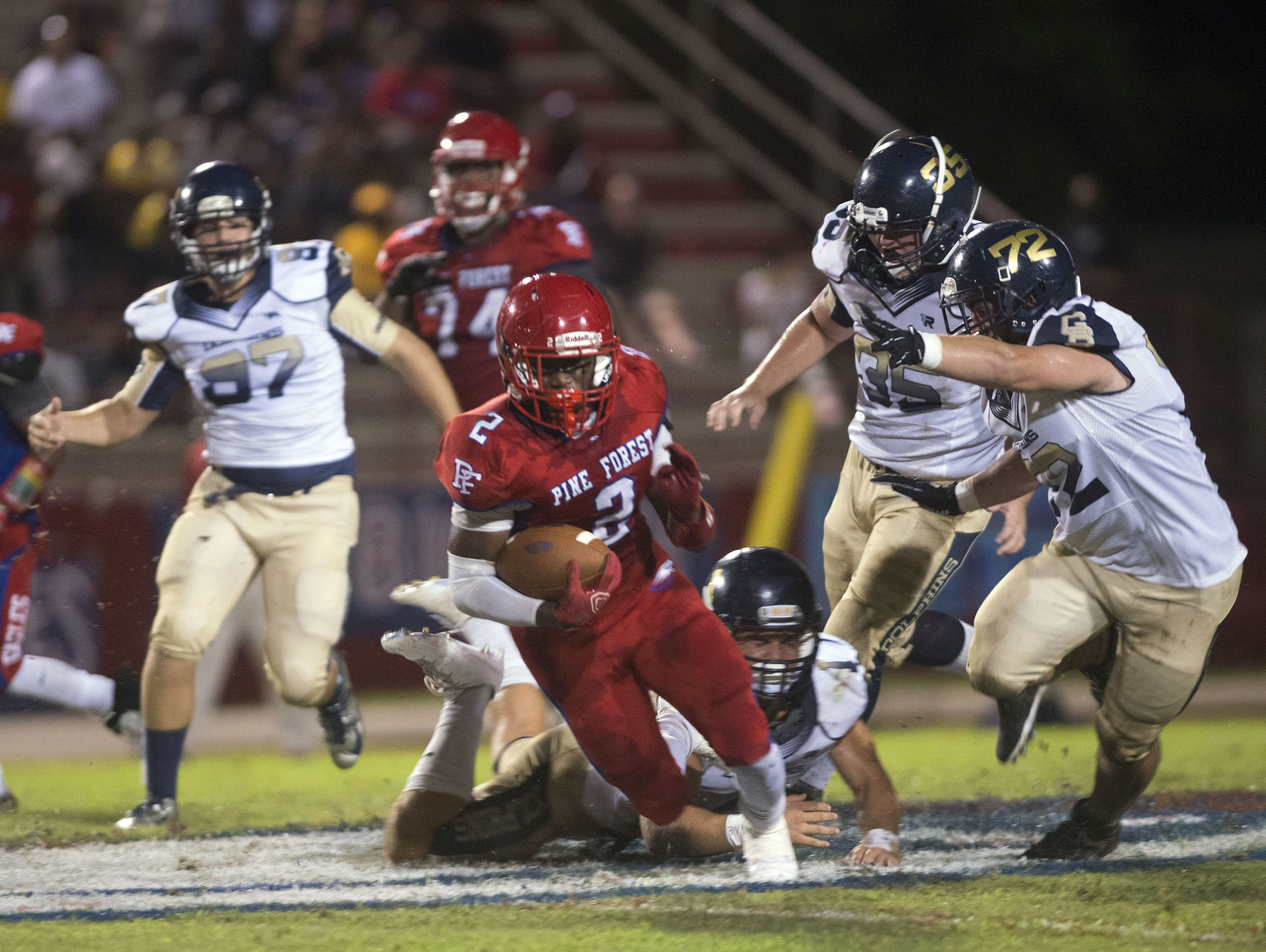 Pine Forest High running back Jaden Gardner, (No.2), slips past the from the Gulf Breeze defense during Friday night's home game against the Dolphins.