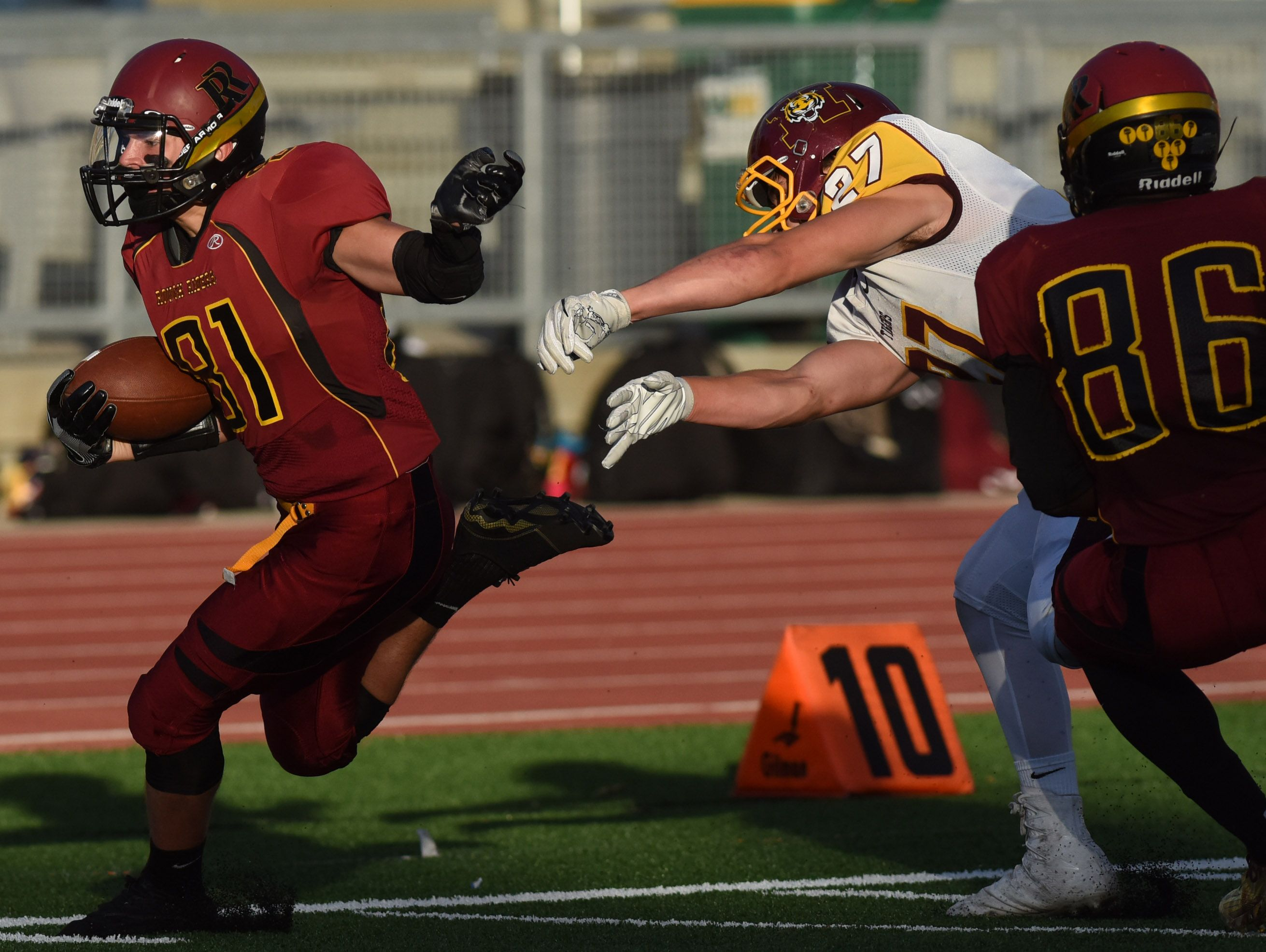 Roosevelt's Austin Johnson runs toward the end zone while Harrisburg's Logan Warzecha tries to stop him during their game on Friday at Howard Wood Field.