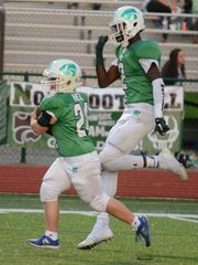 Wildcat wide receiver Traveon Maddox, Jr., right, begins to celebrate as teammate Robby Heil nears the endzone during Novi's Sept. 15 game against South Lyon East.
