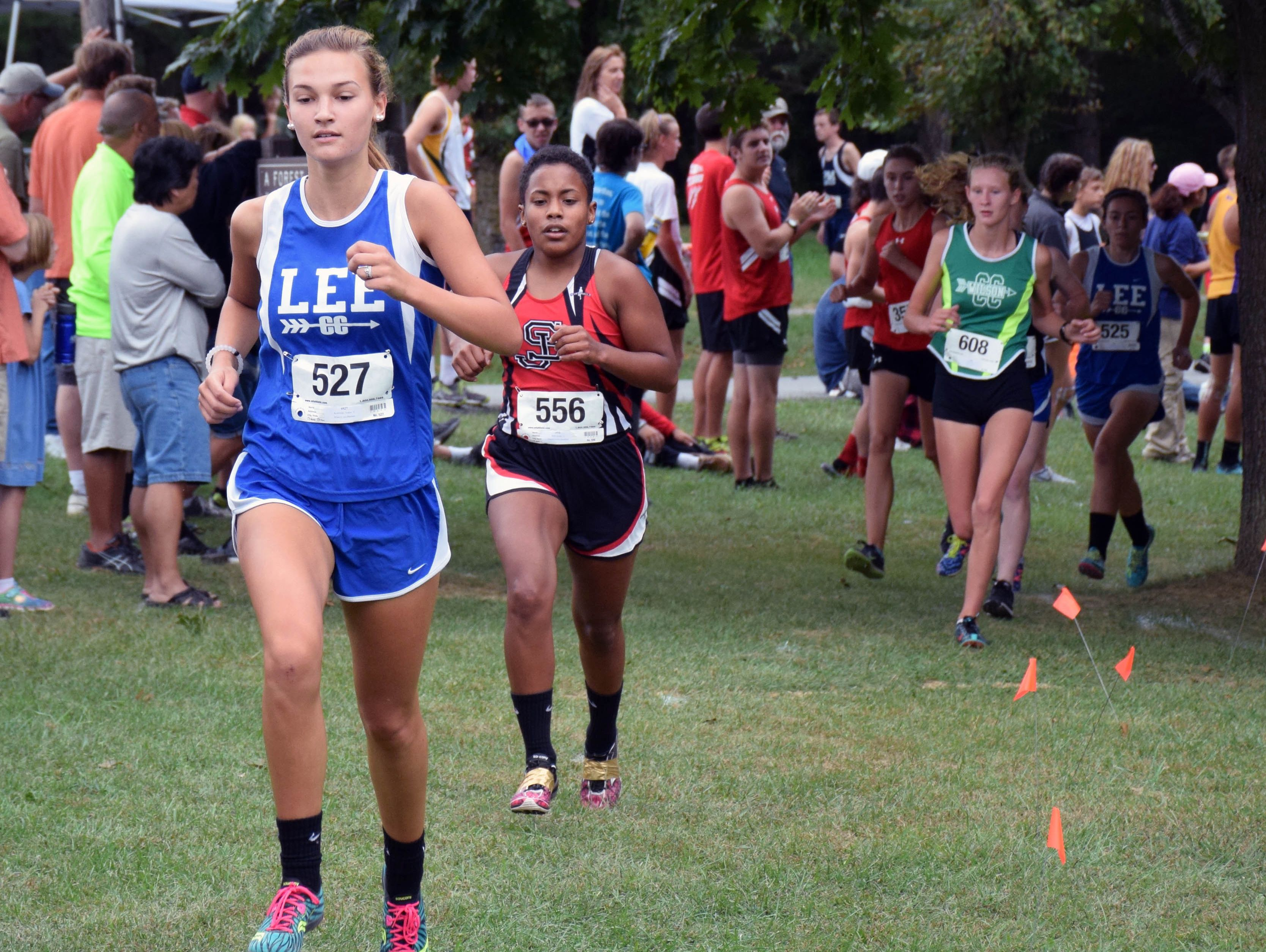 Robert E. Lee's Sophie Kozlowski stays ahead of Stonewall Jackson's Brandy Webb during the varsity girls race at the Augusta County Cross Country Invitational at Wilson Workforce and Rehabilitation Center in Fishersville, Va., on Saturday, Sept. 17, 2016.