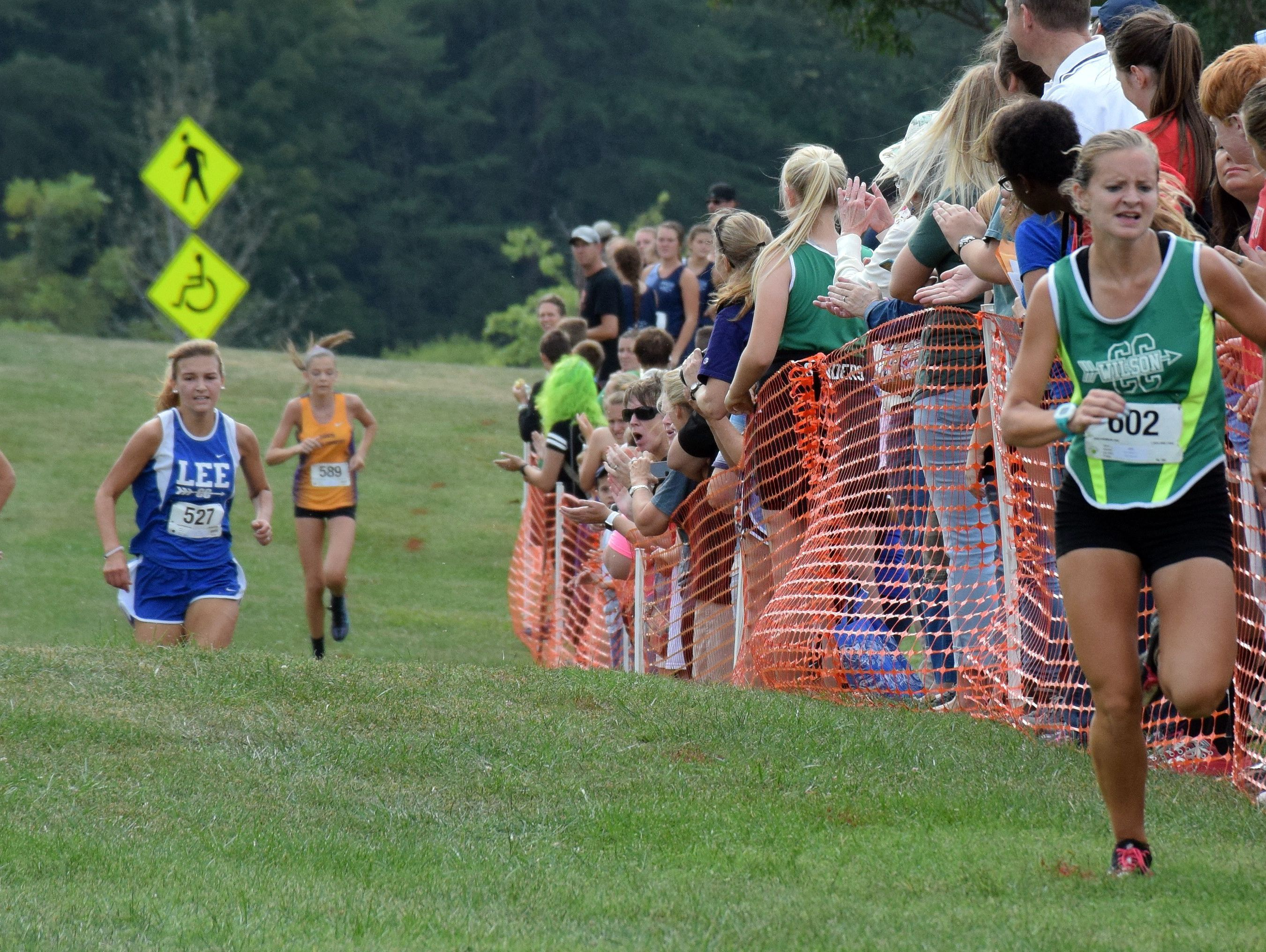 Wilson Memorial's Natalie Prye, right, leads Collegiate's Maddy Watkins, left, and Robert E. Lee's Sophie Kozlowski on her way to winning the varsity girls race at the Augusta County Cross Country Invitational at Wilson Workforce and Rehabilitation Center in Fishersville, Va., on Saturday, Sept. 17, 2016.