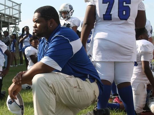 Griffin Middle School assistant coach Antwoine Smith takes a knee during the national anthem before the team's game against Deerlake. (Photo: Jordan Culver/Democrat)