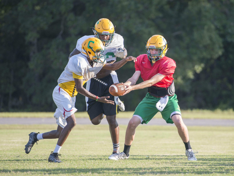Quarterback Garrett Foley hands off the ball during Catholic HS football practice in Pensacola on Wednesday, September 21, 2016.