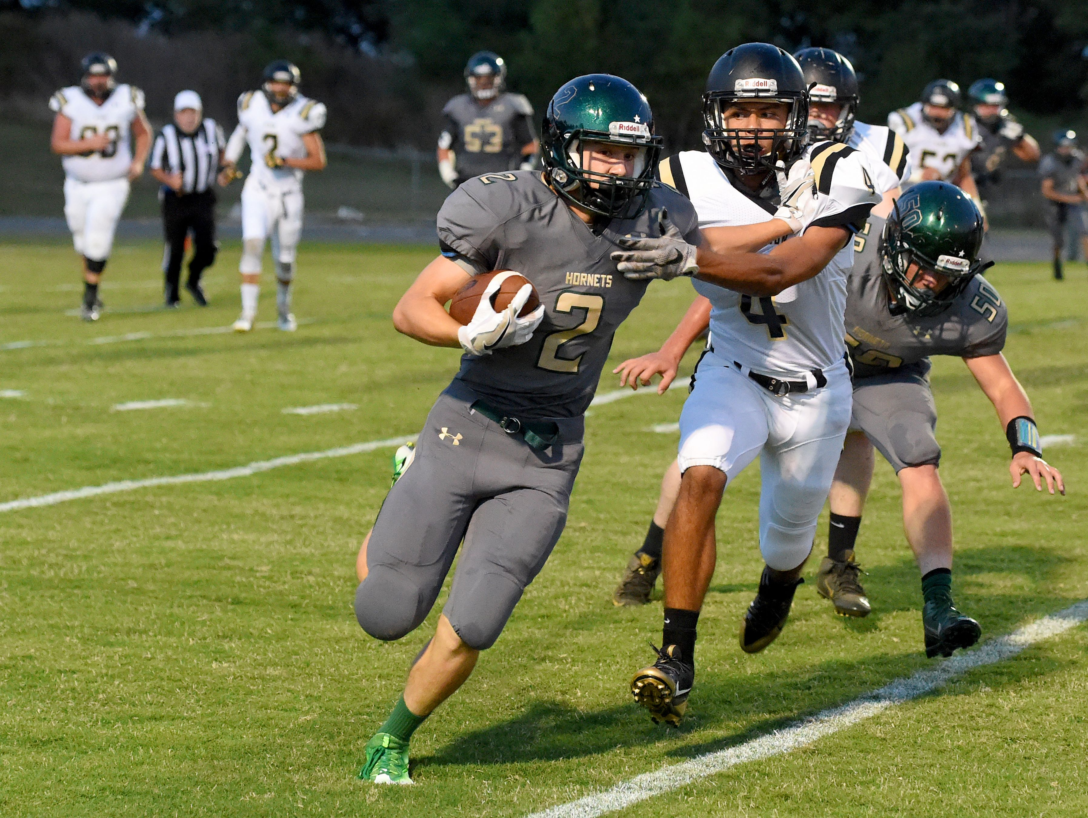 Carrying the football, Wilson Memorial's Colton Tyree pushes off against Buffalo Gap's Jay Johnson who goes for the tackle during a football game played in Fishersville on Friday, Sept. 23, 2016.