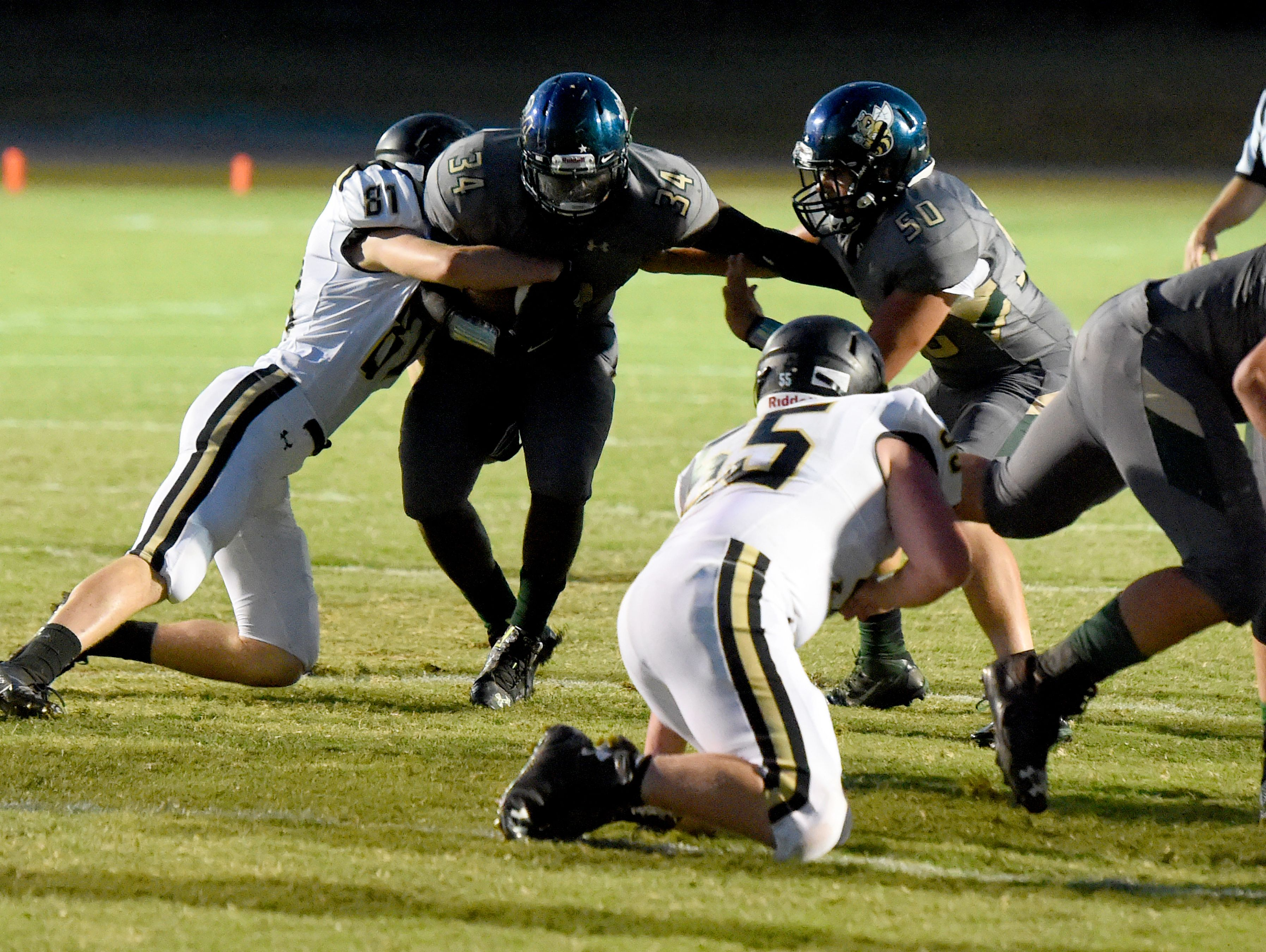 Wilson Memorial's Eddie Harris struggles to move the ball as Buffalo Gap's Carter Mohler goes for the tackle during a football game played in Fishersville on Friday, Sept. 23, 2016.