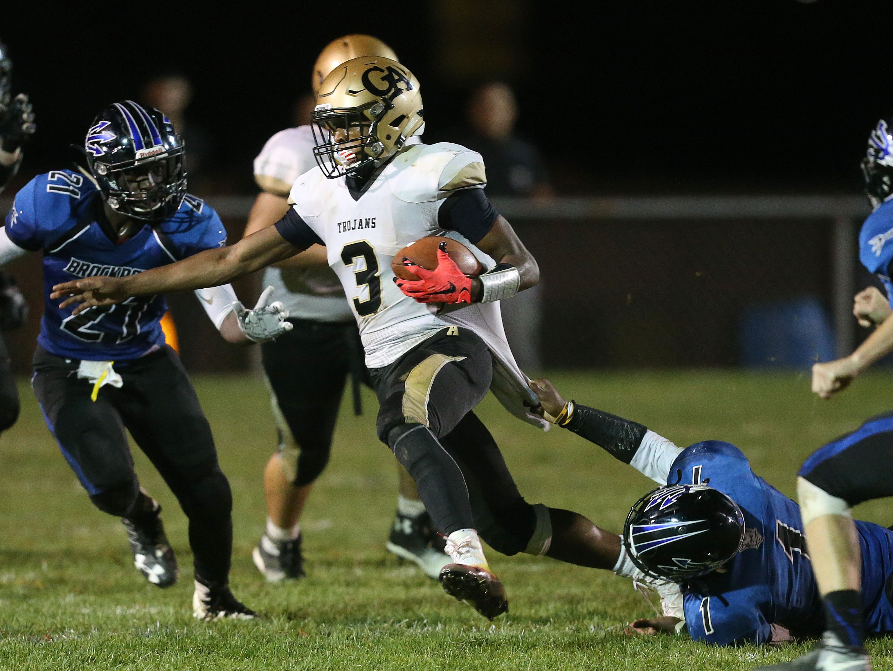 Brockport's Cory Gross hangs on the the shirt tail of Athena quarterback Tavon Granison (3) as he scrambles downfield