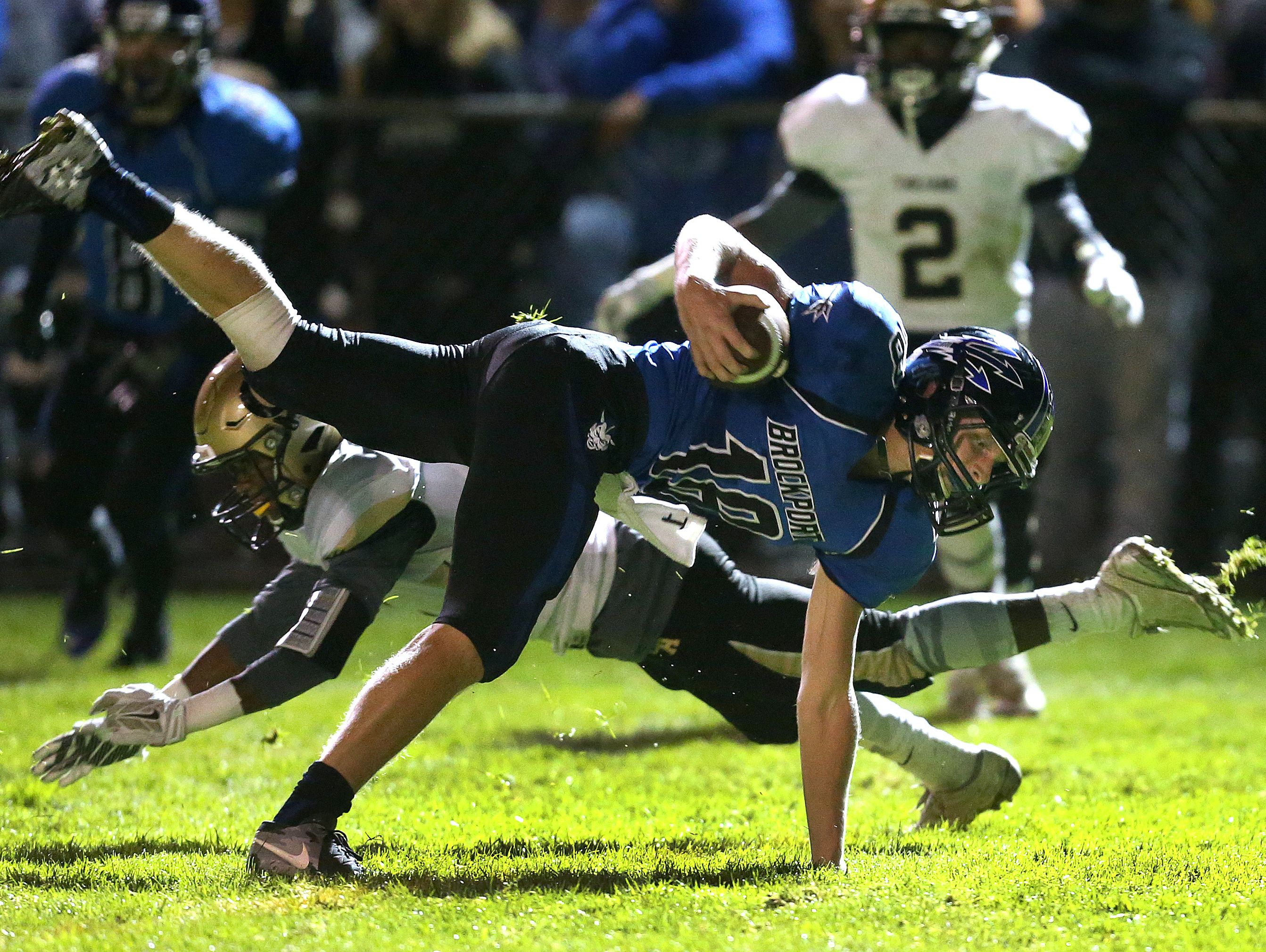 Brockport receiver Nick Brauch (18) is tackled by Athena's Kenny Speed (4) after a catch.