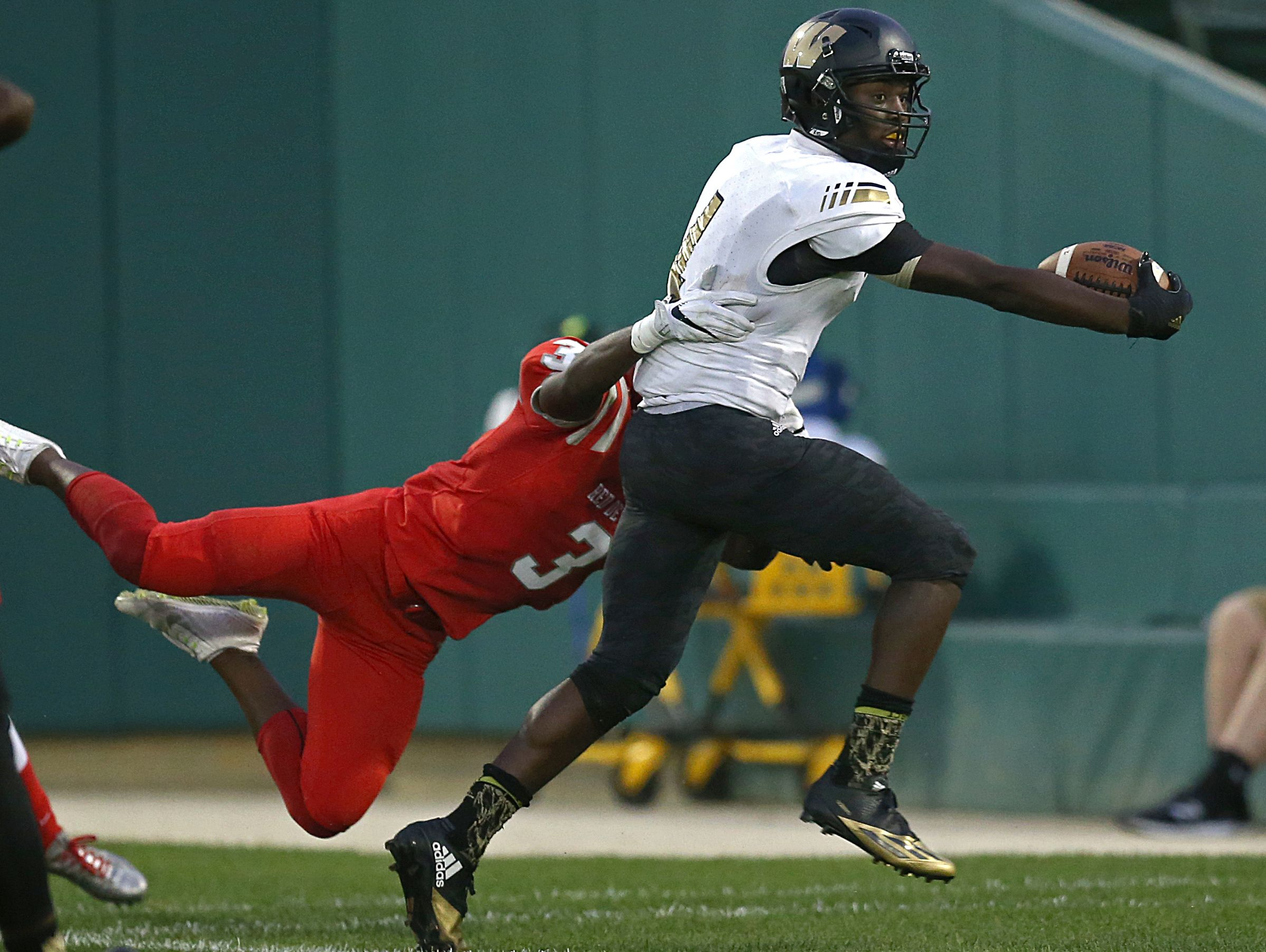 Warren Central Warriors wide receiver David Bell (4) runs in a touchdown despite defense from Pike Red Devils wide receiver Michael Adams (3) during first half action of the Gridiron Classic at Victory Field, Indianapolis, Friday, September 23, 2016.
