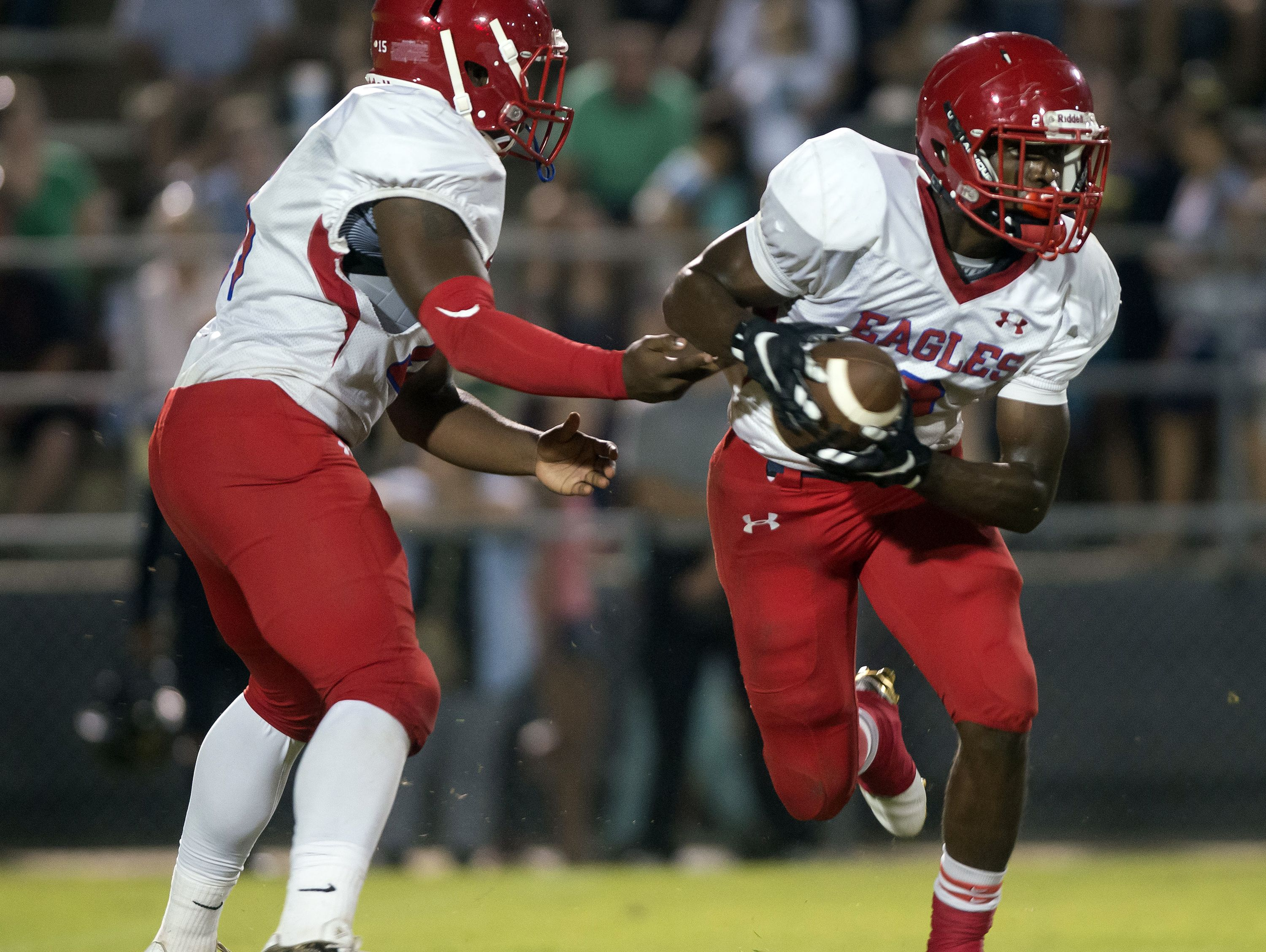 Pine Forest High running back, Jaden Gardner, (No. 2) takes the hand off from quarterback, Xavier Saulsberry (No.15) during the first quarter in Friday night's game against Milton.