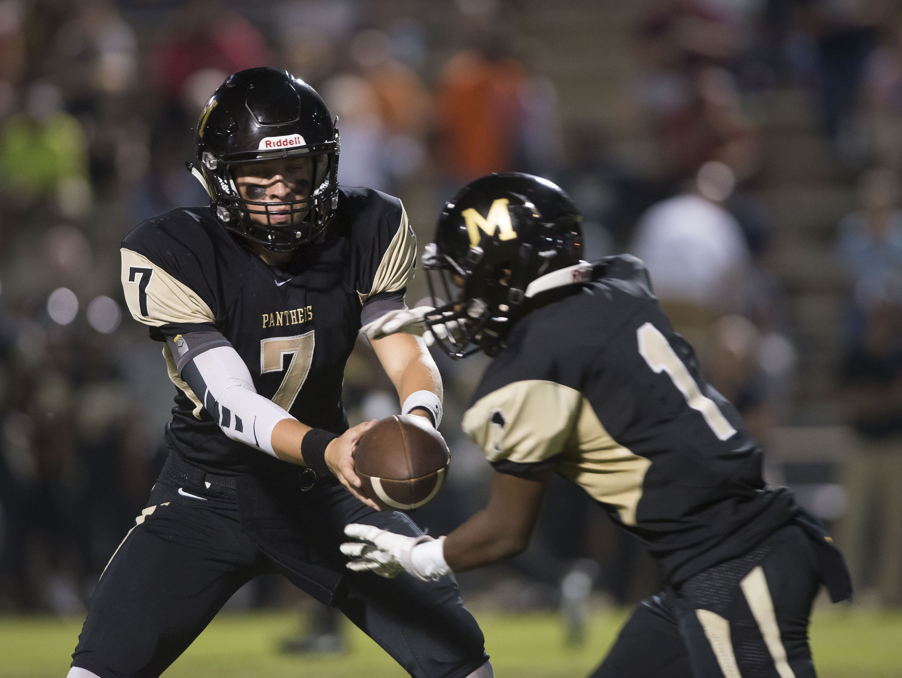 Milton High School quarterback, Aubrey Williams, (No. 7) hands of the ball off to running back Desmone Knight (No.1) during Friday night's game against Pine Forest.