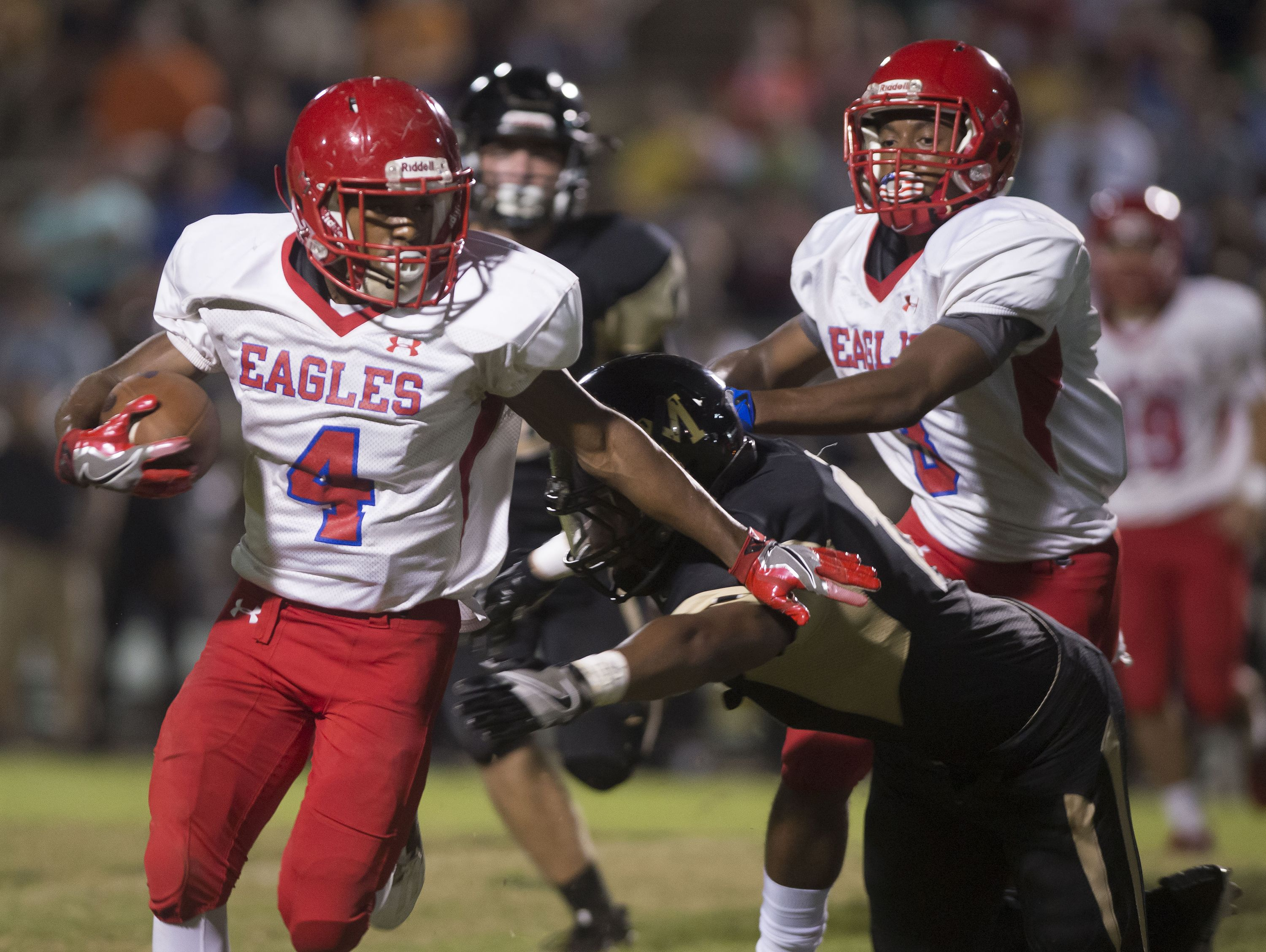 Pine Forest High running back, Ladarius Wiggins, (No. 4) tries to break the tackle of a Milton High defender during Friday night's game against the Panthers.