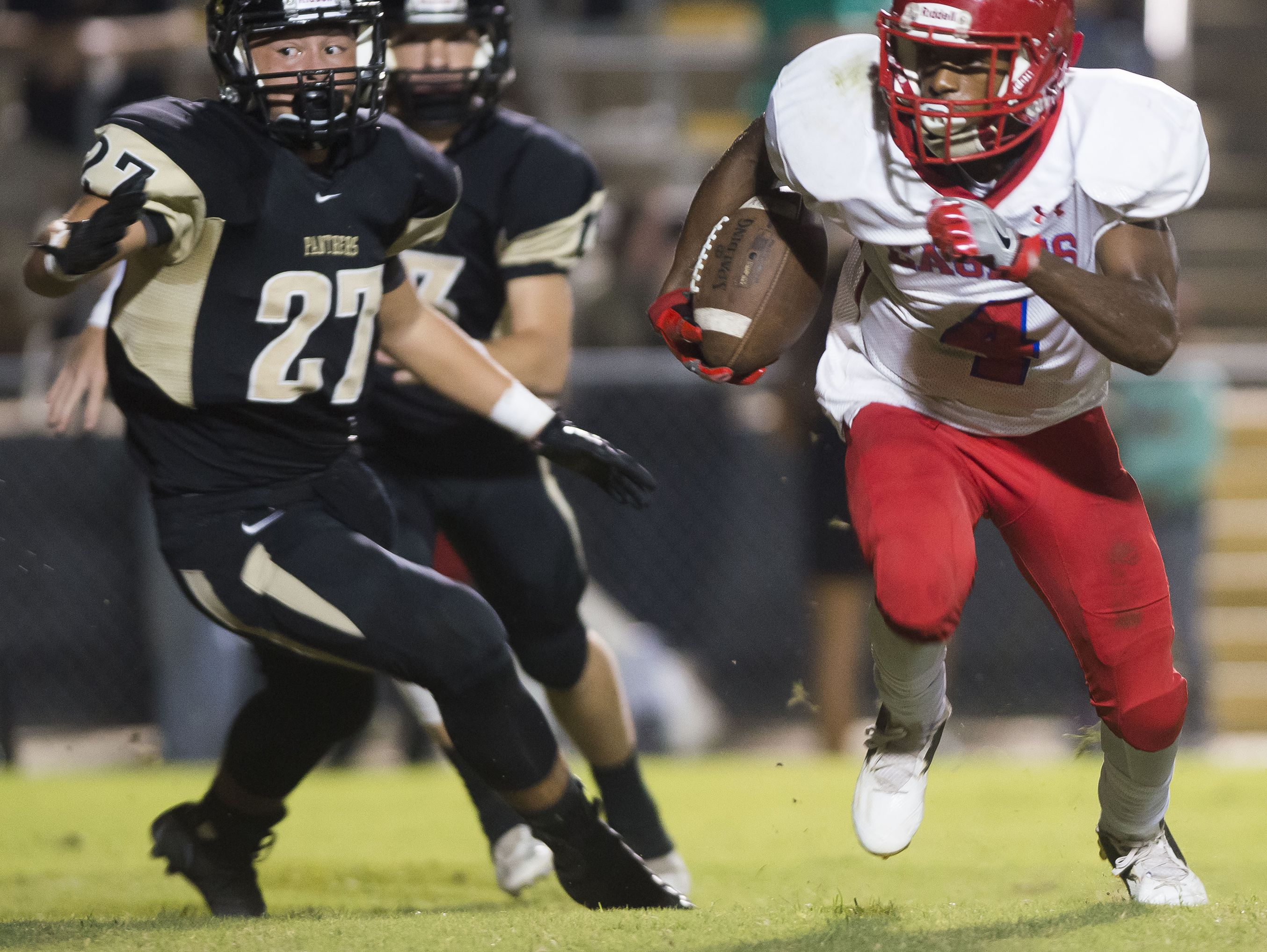 Pine Forest High running back, Ladarius Wiggins, (No. 4) slips past Milton High middle line backer, Michael Mullen, (No. 27) during the first quarter in Friday night's game against the Panthers.