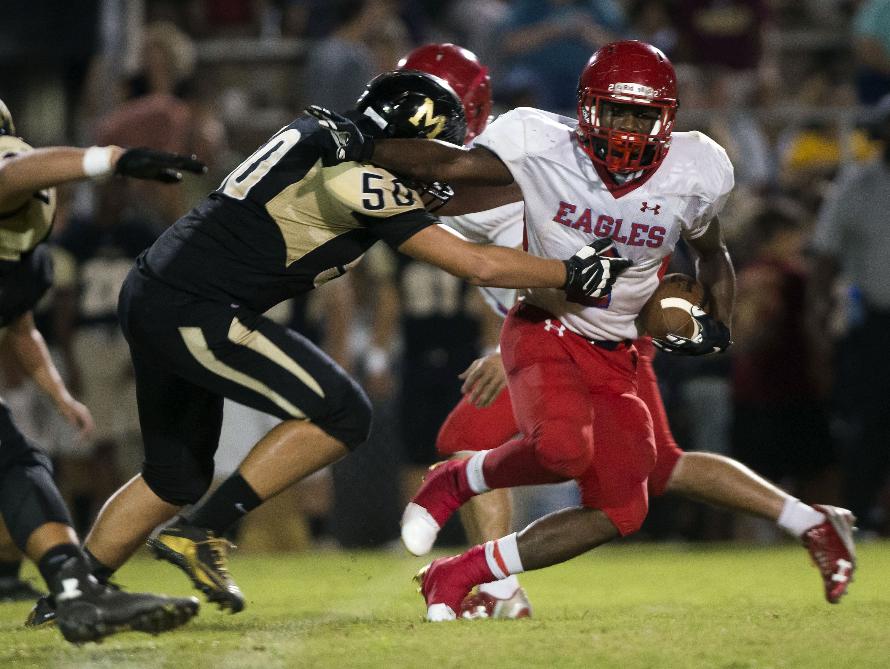 Pine Forest High's Jaden Gardner, (No. 2) gets caught behind the line by Milton High's Keenan Black, (No. 50) during the first quarter in Friday night's game against the Panthers.