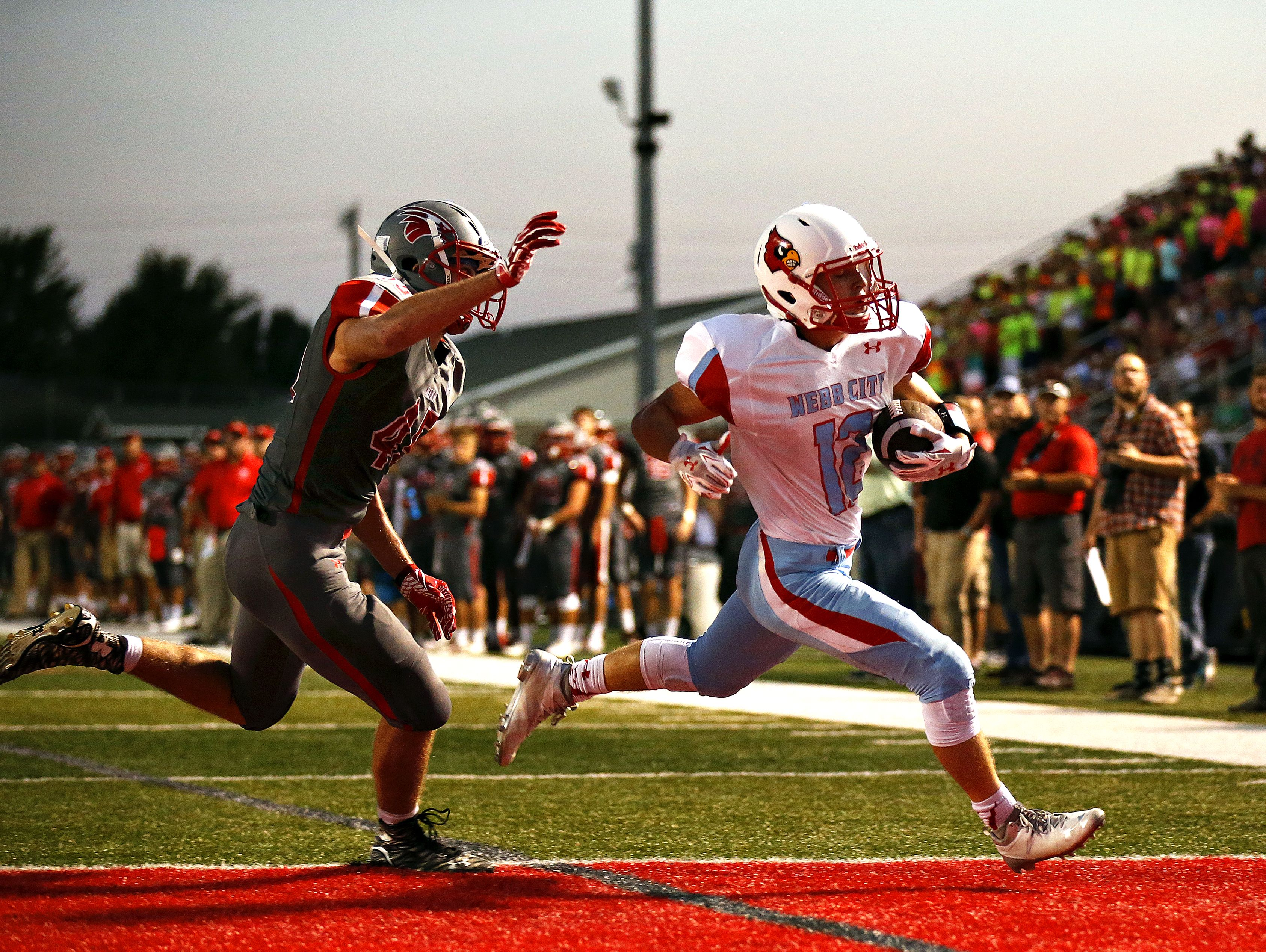 Webb City High School wide receiver Blake Catterson (12) outruns Eagles linebacker Logan Ayers (45) to score a two-point conversion during first quarter action of the football game between Nixa High School and Webb City High School at Eagles Stadium in Nixa, Mo. on Sept. 23, 2016. Webb City won the game 34-10.