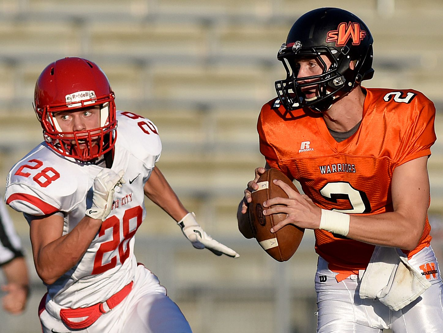 Washington's Jayden Johannsen looks to pass while Rapid City Central's Jordan Ladson chases after during their game on Friday at Howard Wood Field.