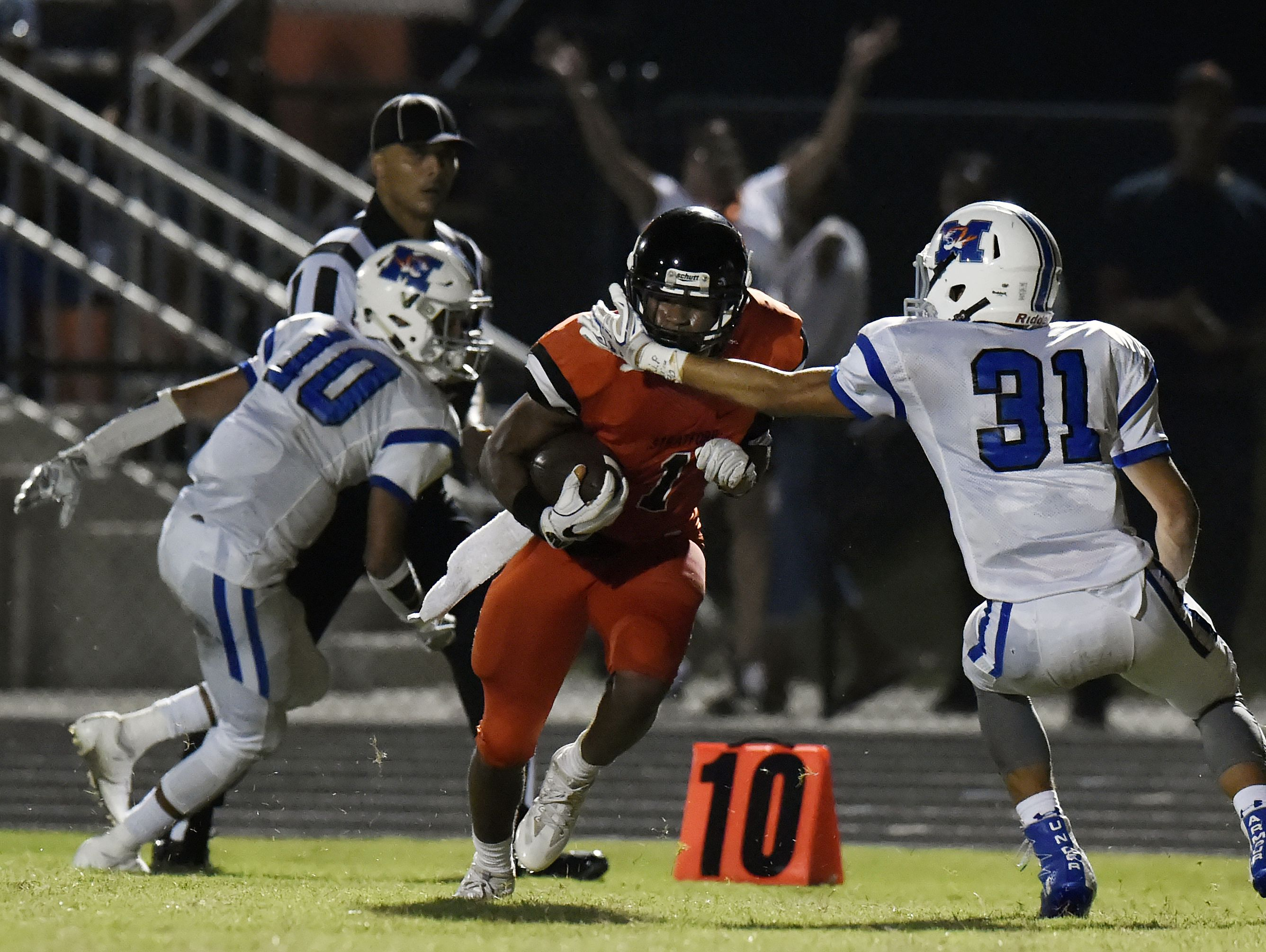 Stratford running back T.J.Carter, center, runs the ball between Marshall County's Tre Crutcher (10) and Donathon Tears (31) after pulling in a pass reception during second half of a high school football game on Friday, Sept. 23, 2016, in Nashville, Tenn. Stratford won 28-21.