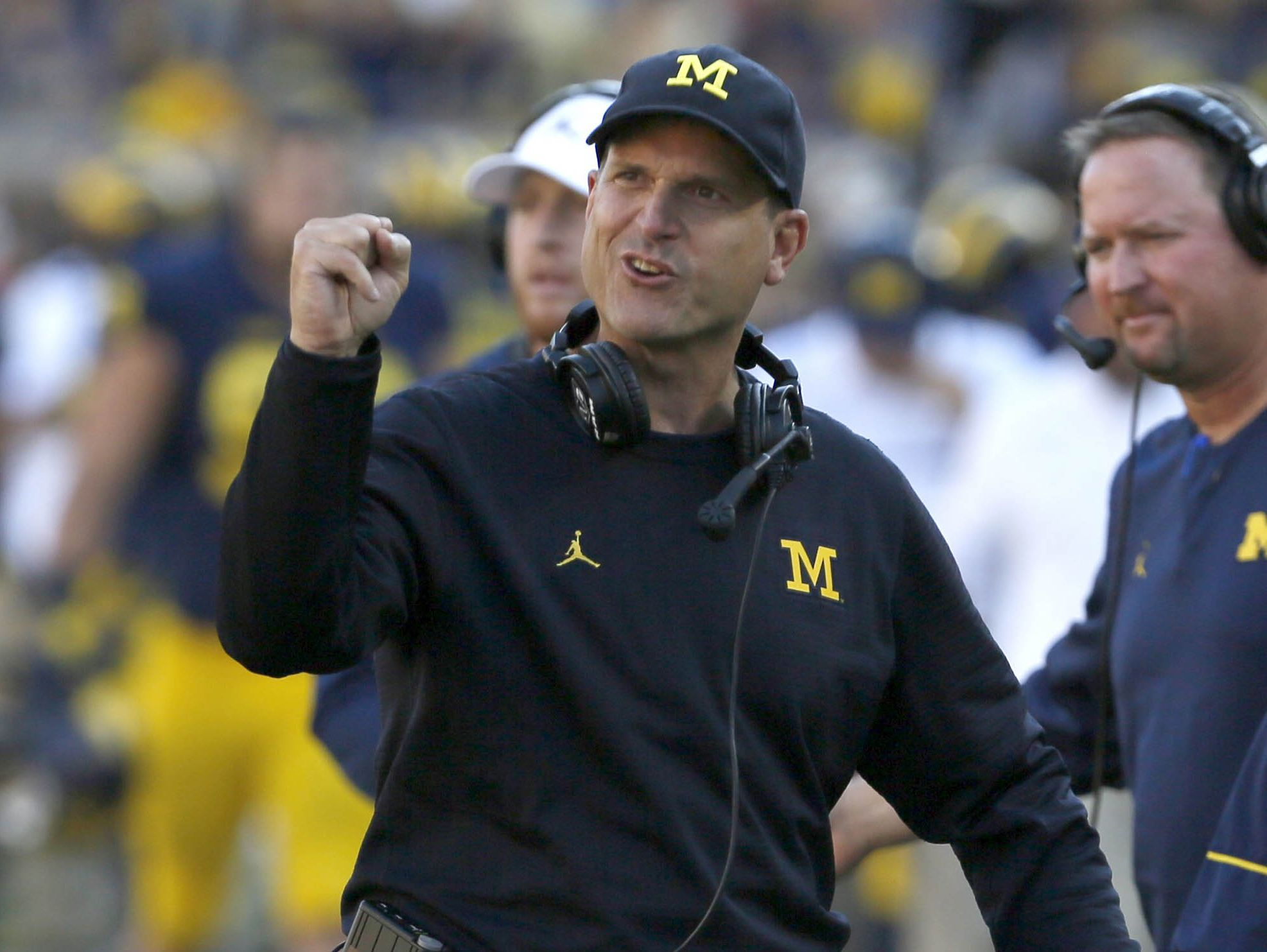 Michigan coach Jim Harbaugh encourages his players coming off the field after another Michigan score making it 21-0 towards the end of the half at Michigan Stadium Saturday.