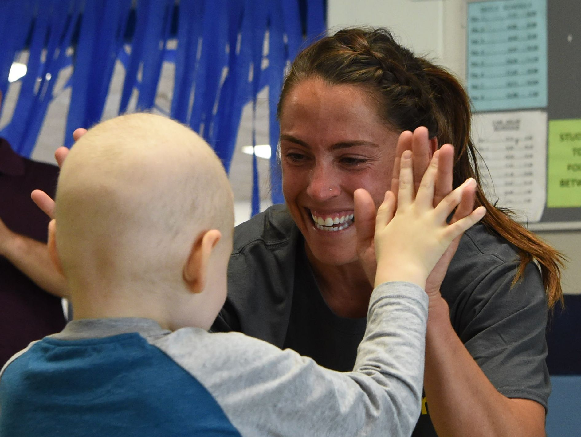 """Kristen Perry, right, a physical education teacher and the field hockey coach at John Jay High School, gives high fives to Liam Craane, 5, who is battling pediatric cancer. The school's field hockey team """"adopted"""" Liam through the Friends of Jaclyn Foundation."""