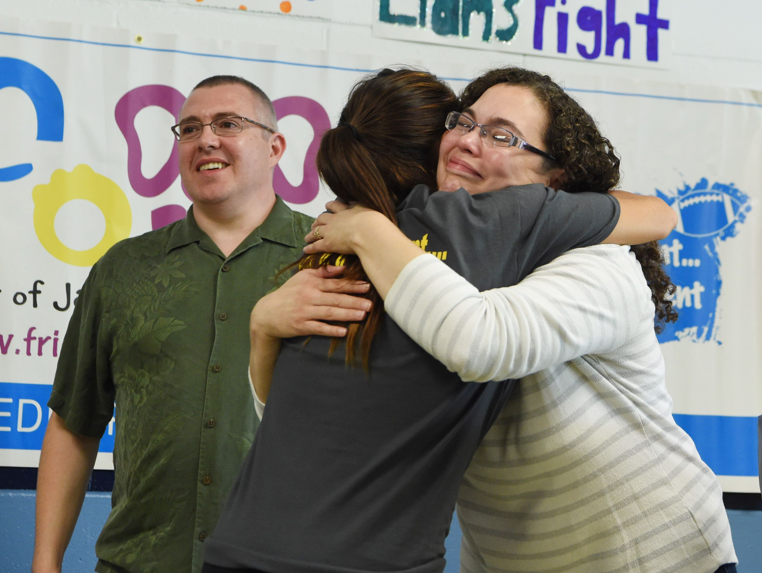 """Kristen Perry, center, a physical education teacher and the field hockey coach at John Jay High School, gives a hug to Jeanmarie Craane, right. The school's field hockey team """"adopted"""" Craane's son Liam, 5, who is battling pediatric cancer, through the Friends of Jaclyn Foundation."""