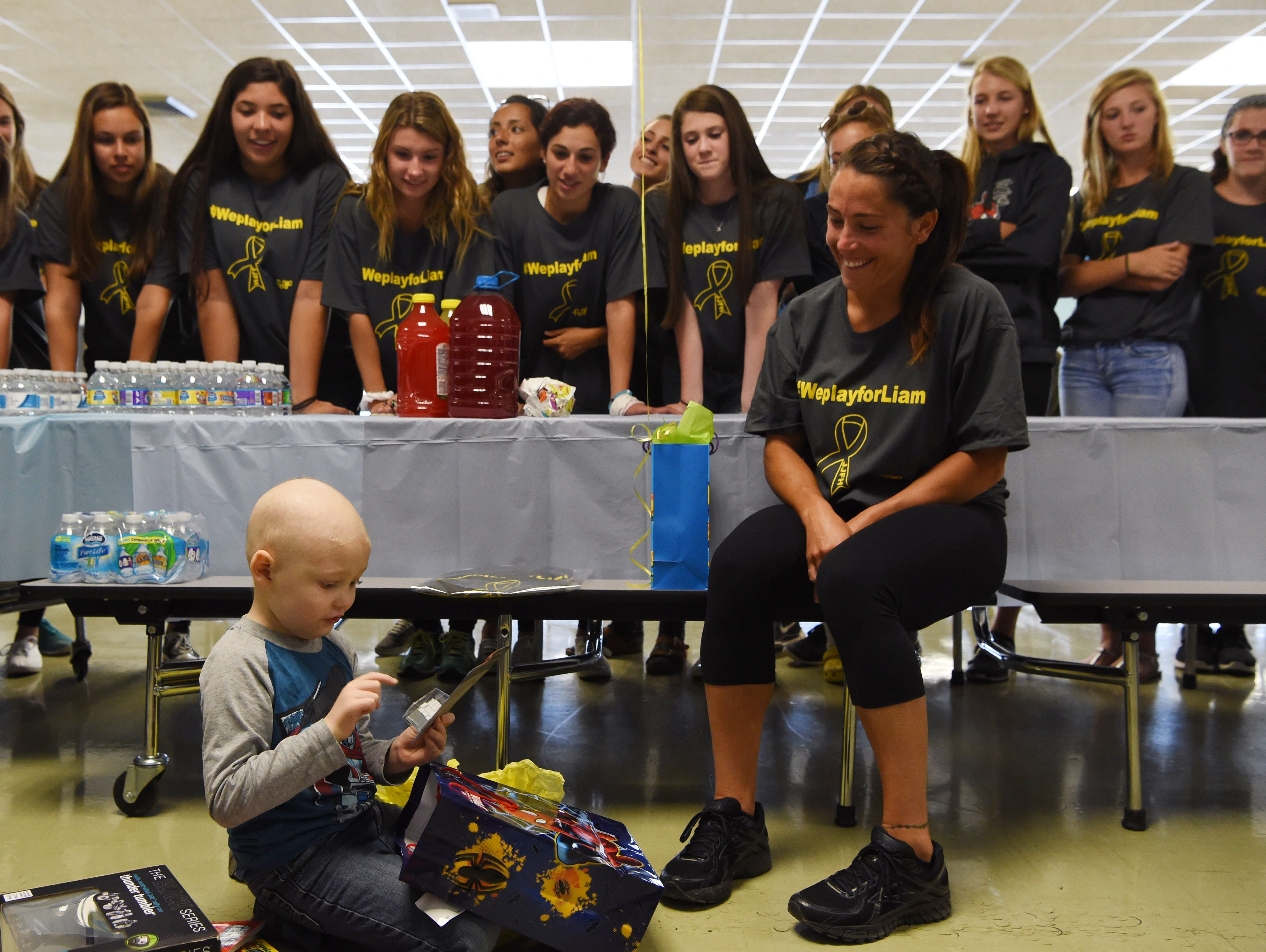 """Liam Craane, 5, left, who is battling pediatric cancer, opens presents given to him by the John Jay field hockey team. Liam was """"adopted"""" by the team through a program created by the Friends of Jaclyn Foundation. Sitting at left is field hockey coach and physical education teacher Kristen Perry."""