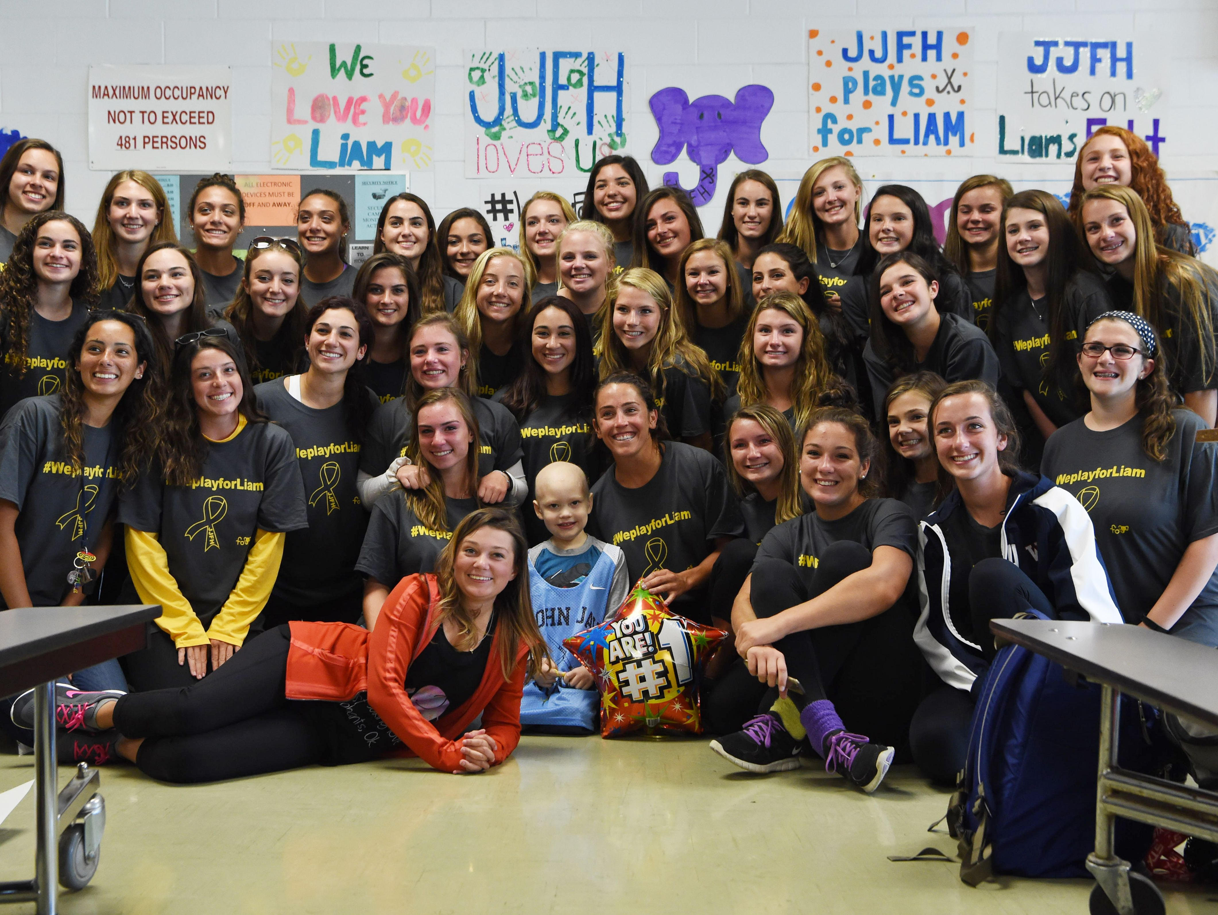 """The John Jay field hockey team poses with Liam Craane, 5, who is battling pediatric cancer. The team """"adopted"""" him as part of a program created by the Friends of Jaclyn Foundation."""