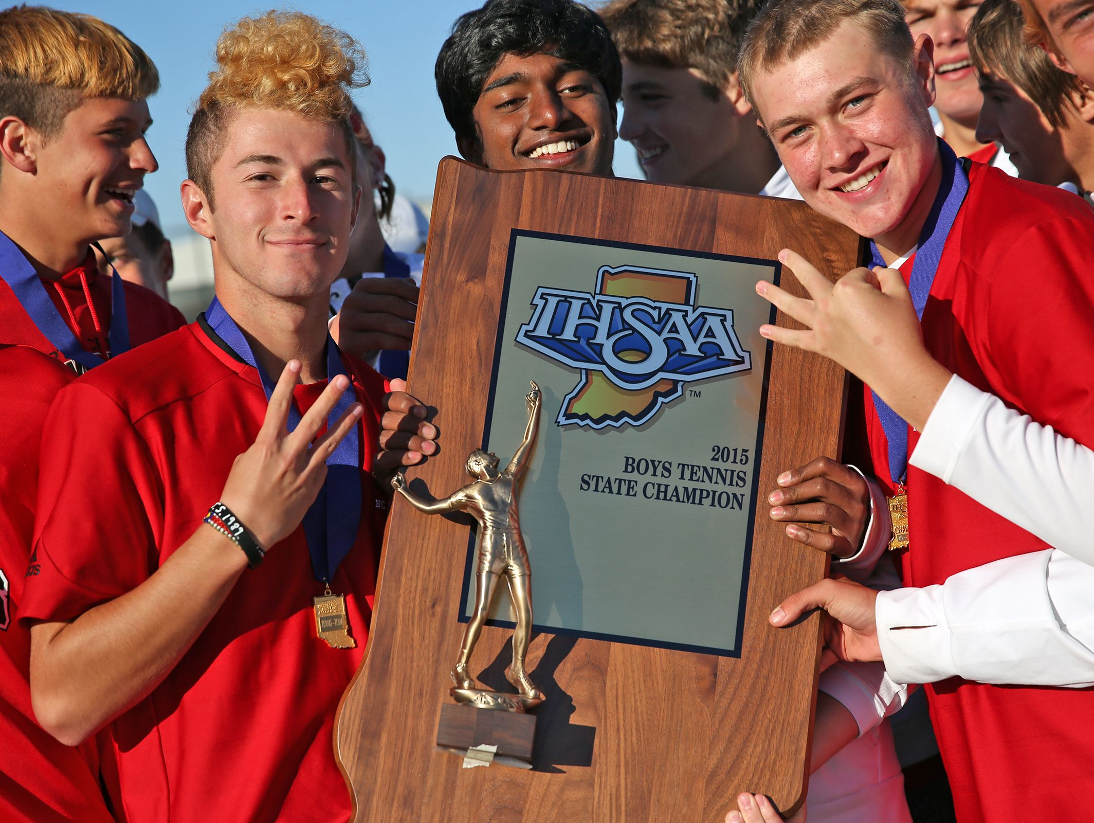 FILE – North Central boys tennis players celebrate their third straight state championship, Oct. 17, 2015.