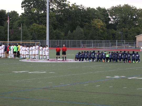 School 58/World of Inquiry boys soccer players kneel during the national anthem prior to their game Tuesday with Aquinas. (Photo: Provided by Rochester Indy Media)