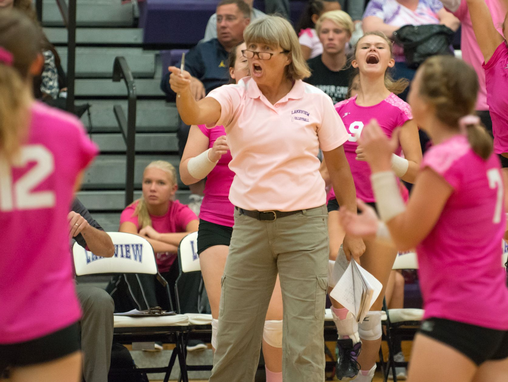 Lakeview head coach Heather Sawyer signals to her players as they win the first match against Mattawan Wednesday night, 30 to 28.