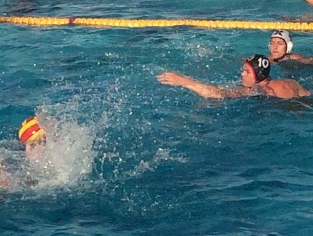 Palm Desert's Ryan Sawyer (black cap) and Xavier Prep's Troy Boydstun (white cap) battle for a loose ball during their water polo match Thursday at Palm Desert.