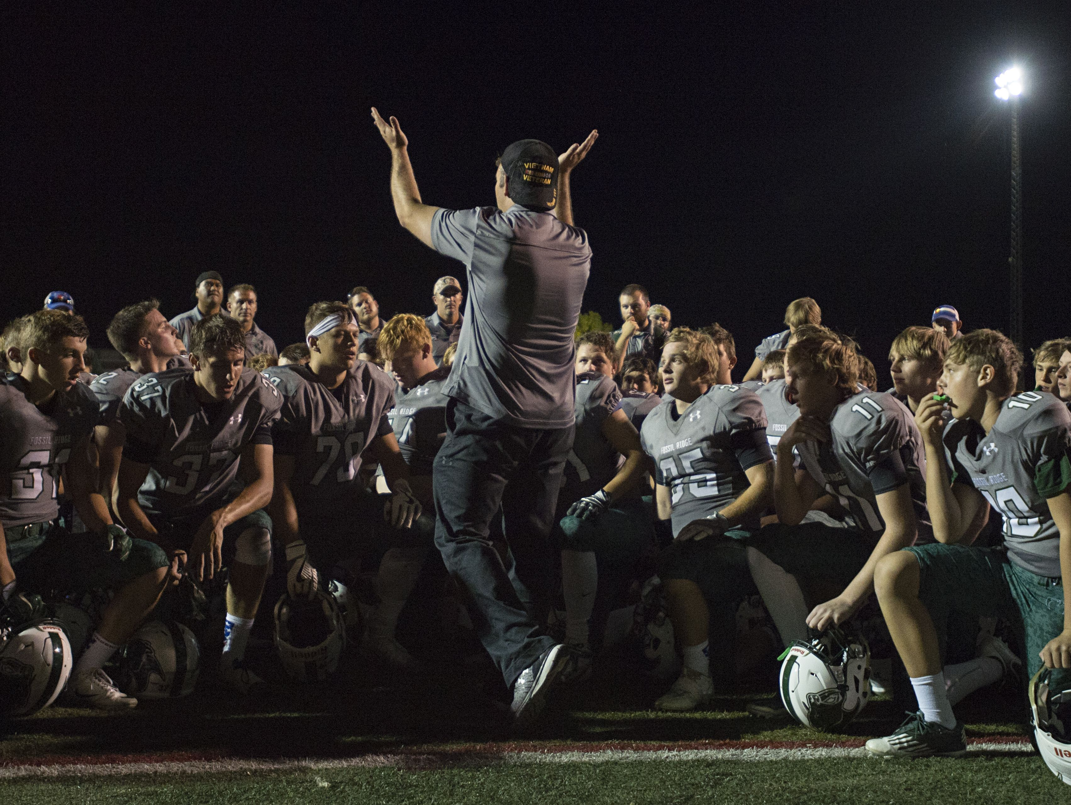 Fossil Ridge coach Zak Bigelow congratulates the SaberCats on a 27-14 win over Lakewood at French Field Thursday.