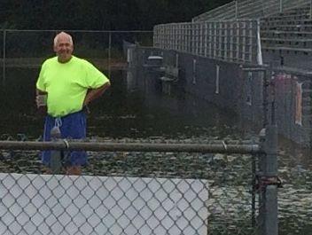 Delmar High School football coach David Hearn surveys flooding at the school's Francis E. Nunvar Stadium on Friday morning.