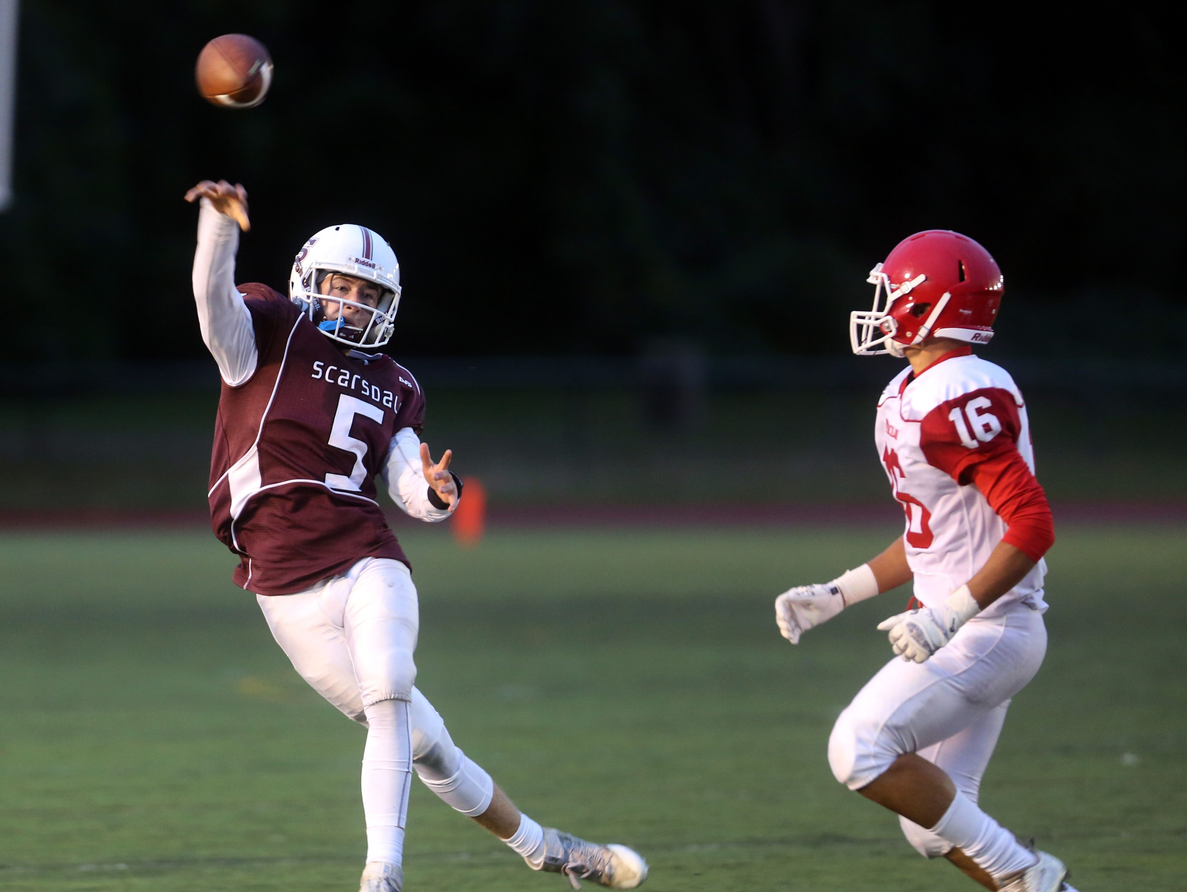 Scarsdale quarterback Robert Rolfe passes while being pursued by North Rockland's Nasier Vasquez during a varsity football game at Scarsdale High School Sept. 30, 3016. Scarsdale defeated North Rockland 31-7.