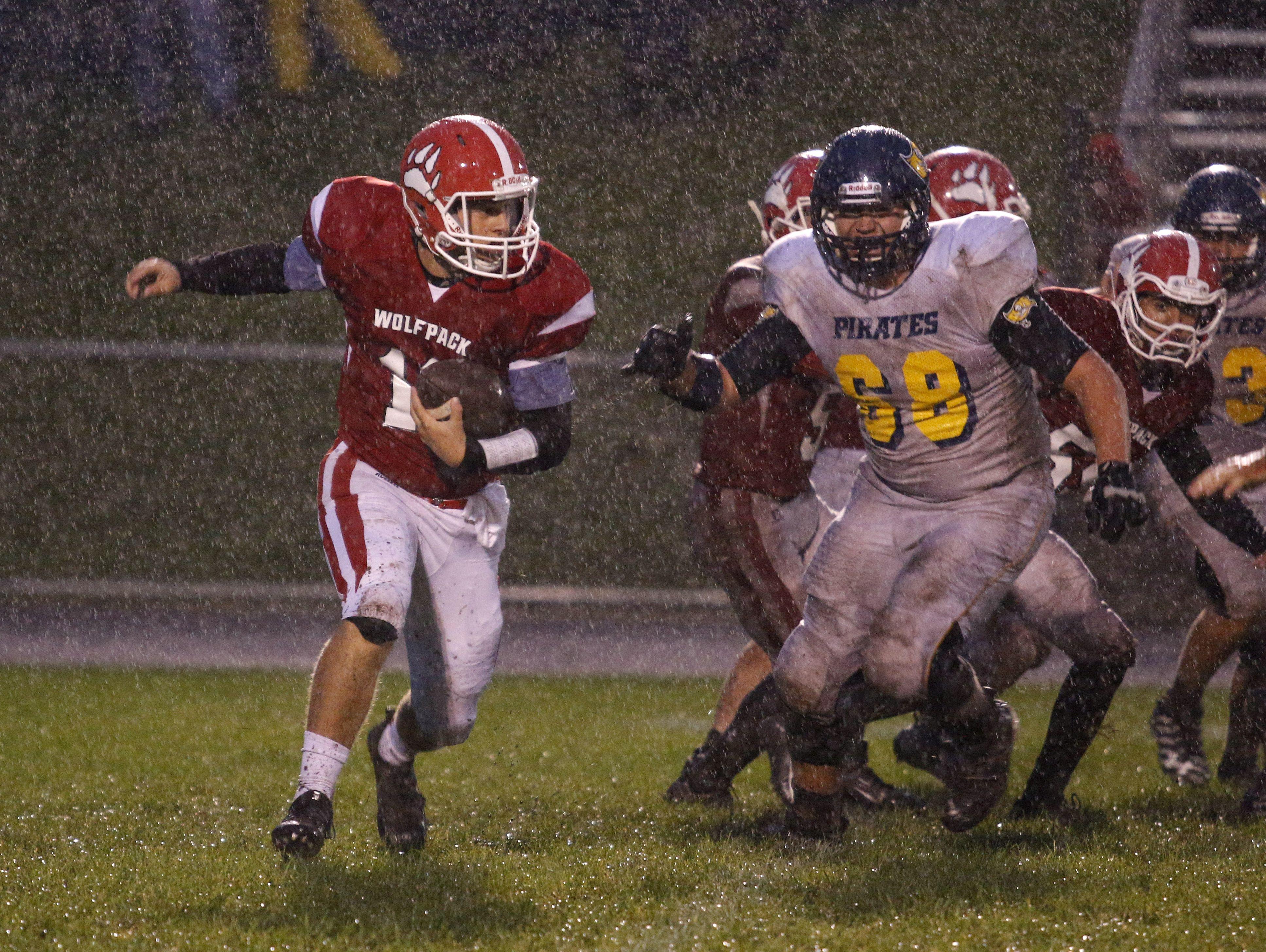 Laingsburg quarterback Nick Putnam, left, runs on a keeper against Pewamo-Westphalia's Isaiah Schafer Friday, Sept. 30, 2016, in Laingsburg, Mich.