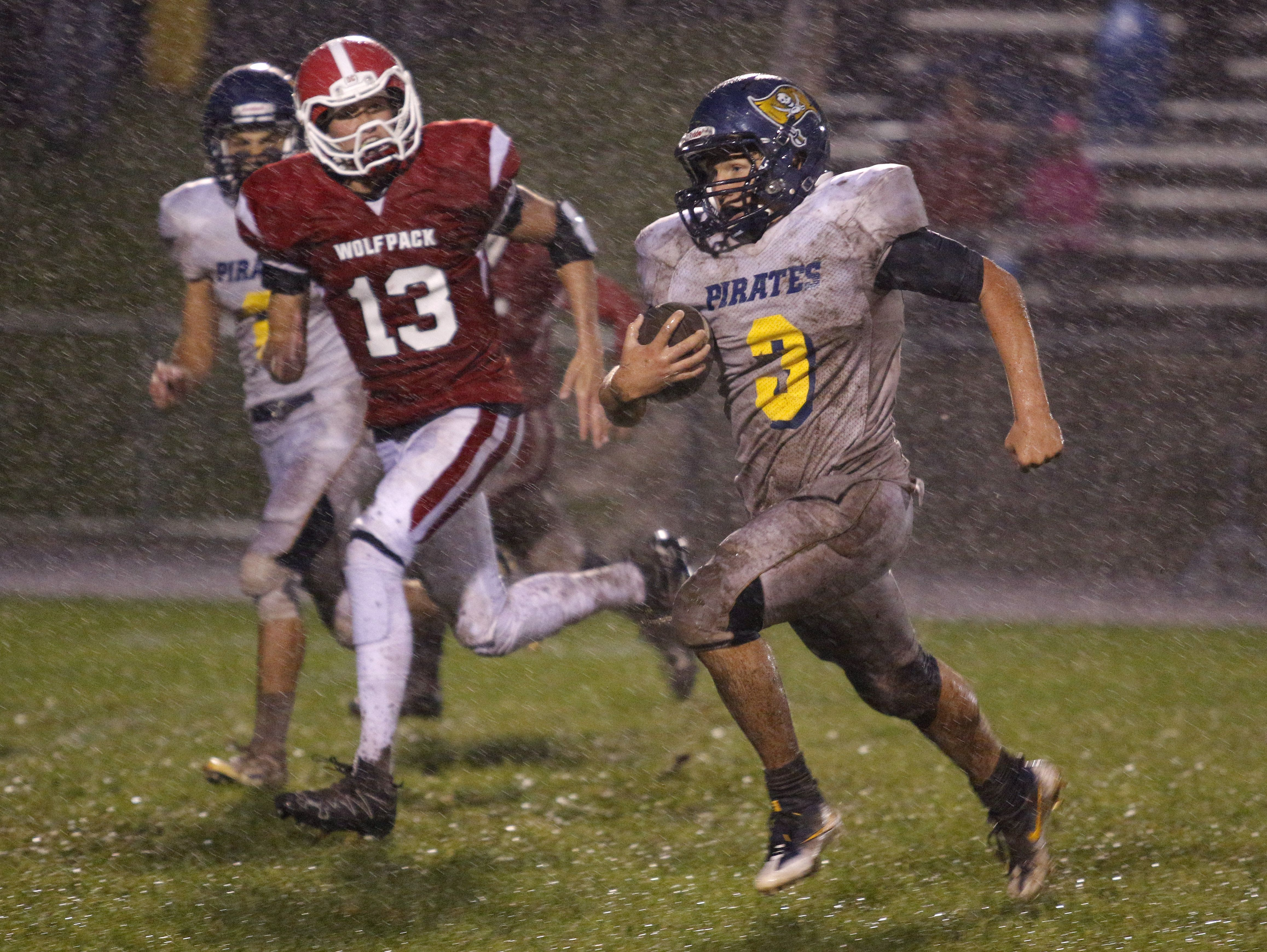 Pewamo-Westphalia quarterback Ryan Smith, right, runs for a touchdown on a keeper against Laingsburg's Jordan Jones (13) Friday, Sept. 30, 2016, in Laingsburg, Mich.