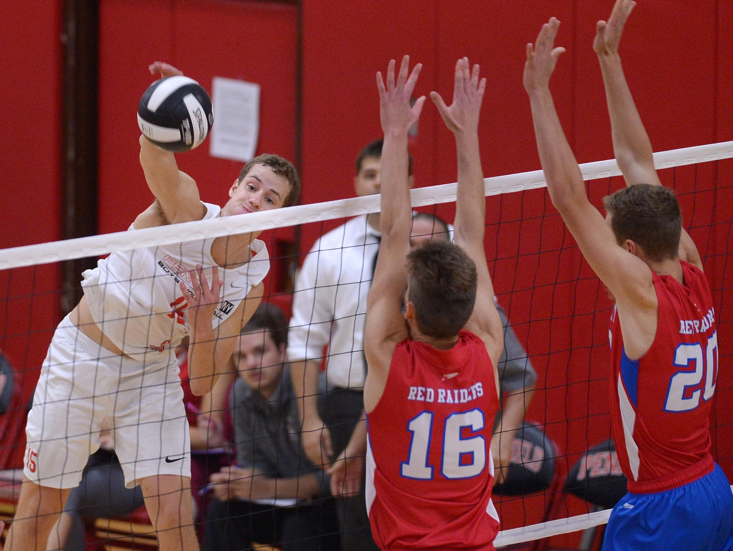 Penfield's Jack Bittker, left, hits by the block of Fairport's Mitch D'Agostino (16) and Garrett Vermeulen on Sept. 20. The Patriots won the match against Fairport in three games.