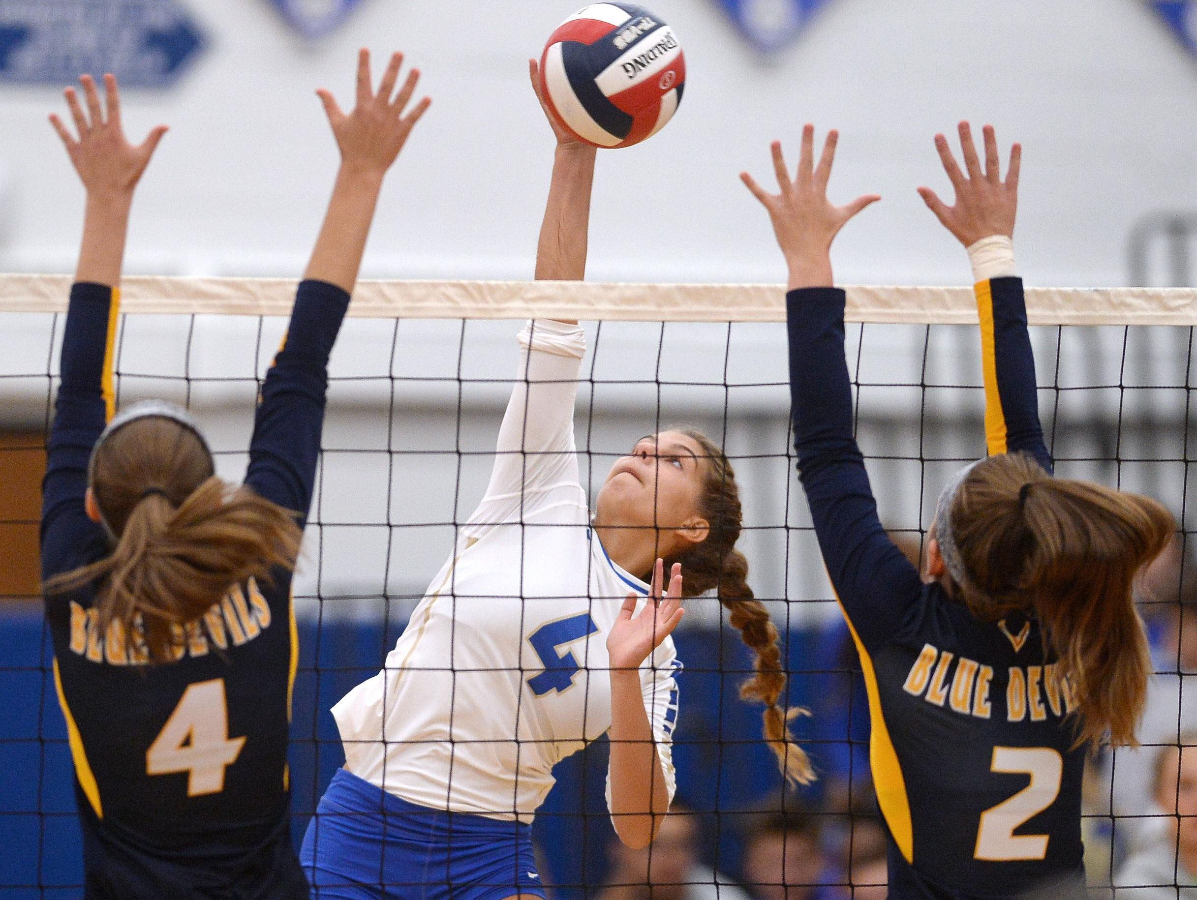 Webster Schroeder's Leigha Kircher hits between the blocks of Victor's Courtney Hannel (4) and Ally Devitte.