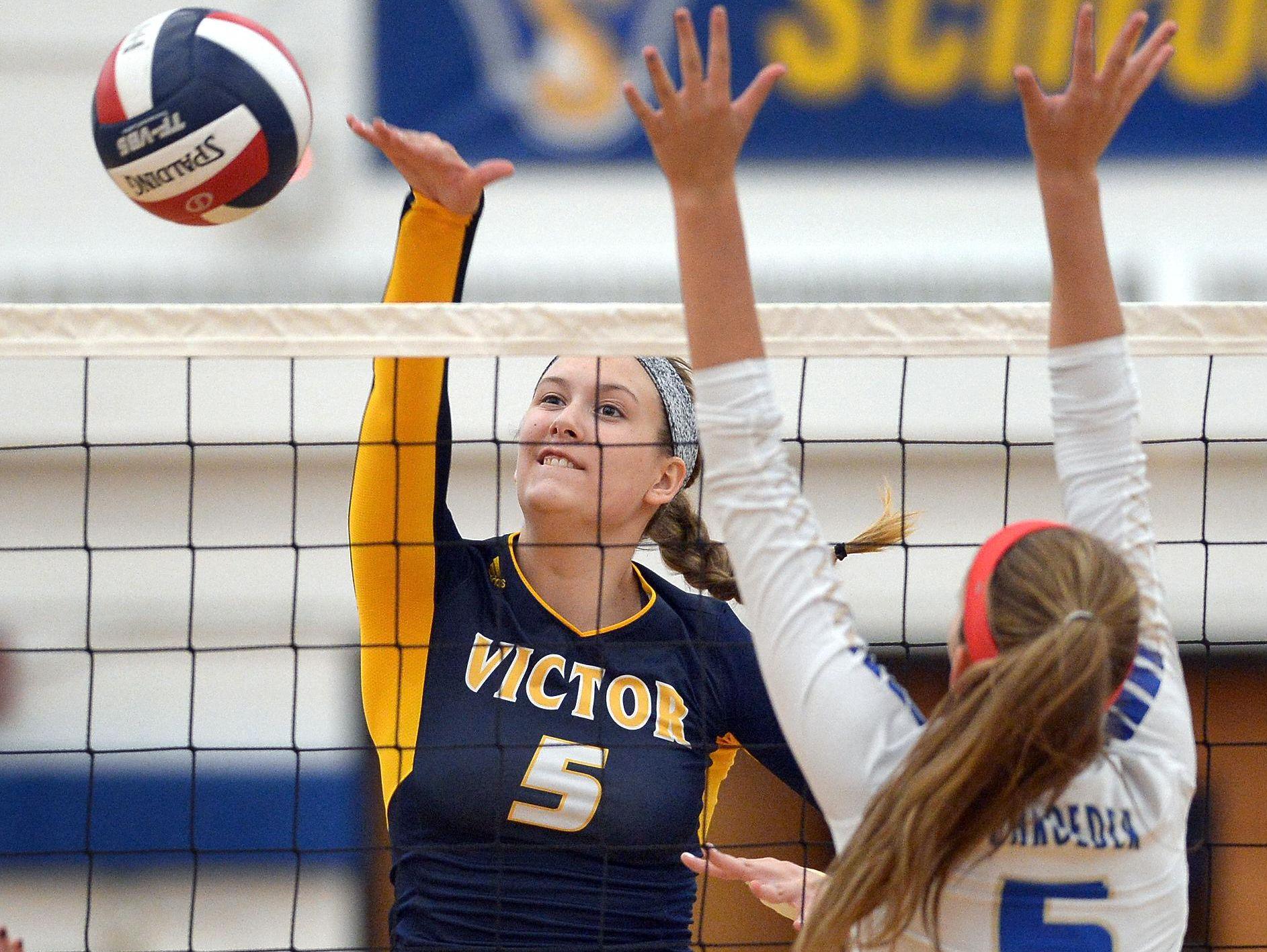 Victor's Makenzie Bills hits past the block of Webster Schroeder's Emma Draper.