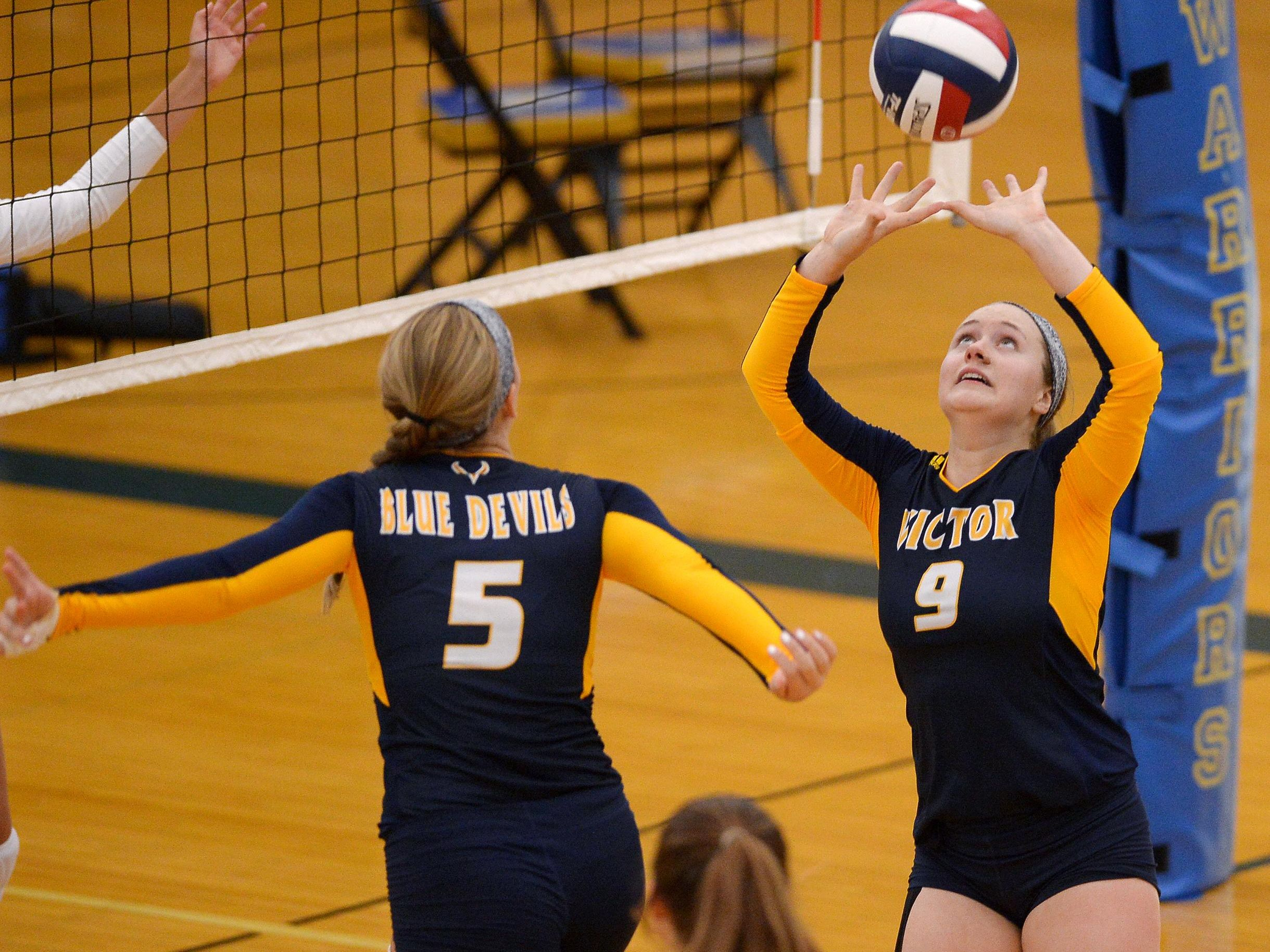 Victor's Emily Weed, right, sets the ball for Makenzie Bills.